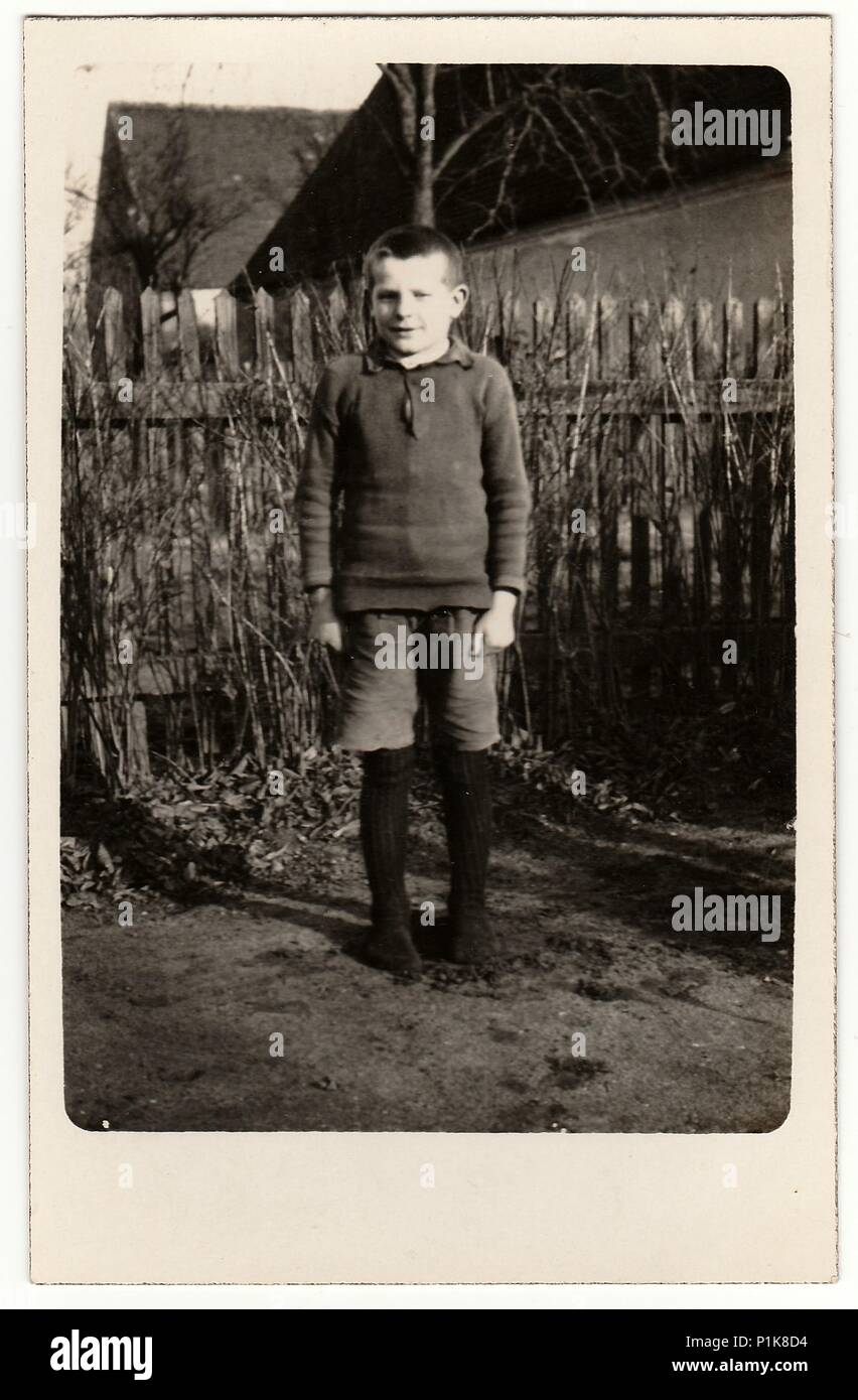 GERMANY - CIRCA 1940s: Vintage photo shows young boy (pupil, student) stands in front of wooden fence. Black & white antique photography. - Stock Image