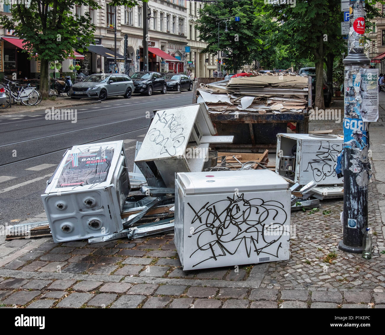 Berlin Prenzlauer Berg.Kastanienallee. Old kitchen white goods dumped on an urban pavement next to a skip - Stock Image