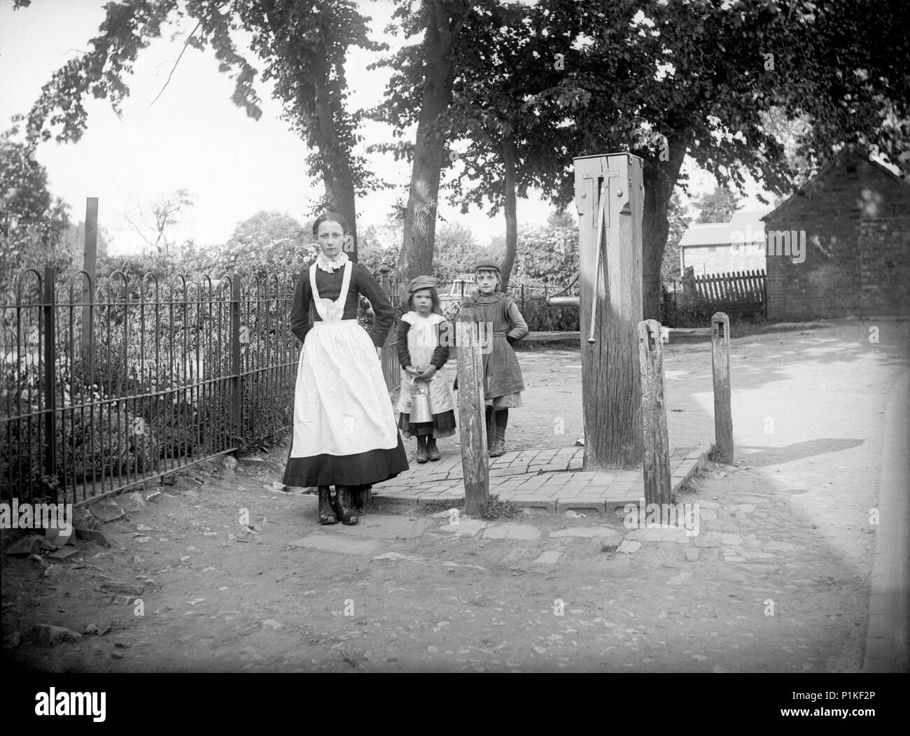 Village pump, Grandborough, Warwickshire, 1901. A young servant girl has been sent to fetch water from the village pump. Two urchins are on a similar  Stock Photo