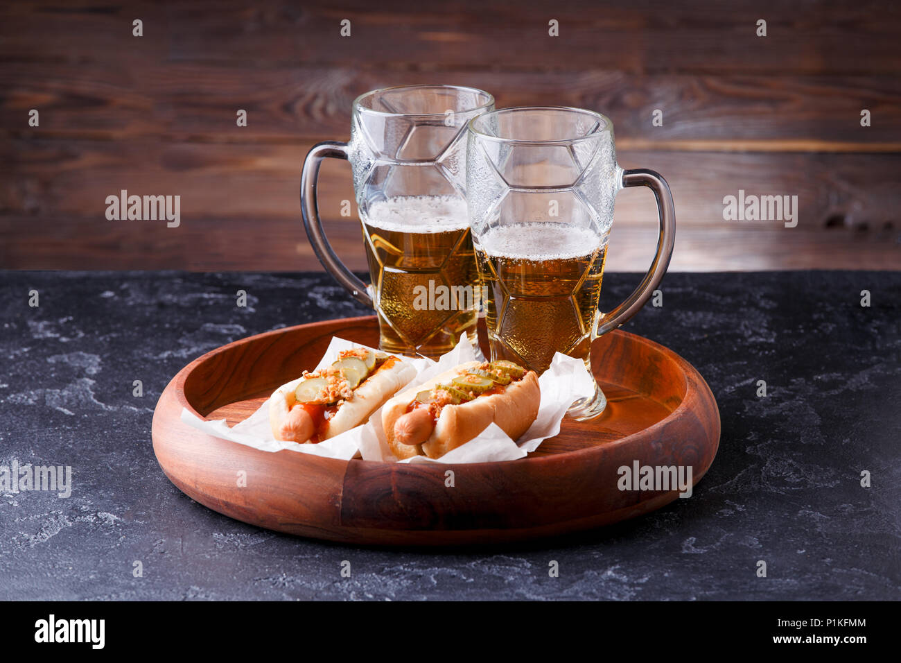 Photo of two mugs of beer and hot dogs on wooden tray Stock Photo