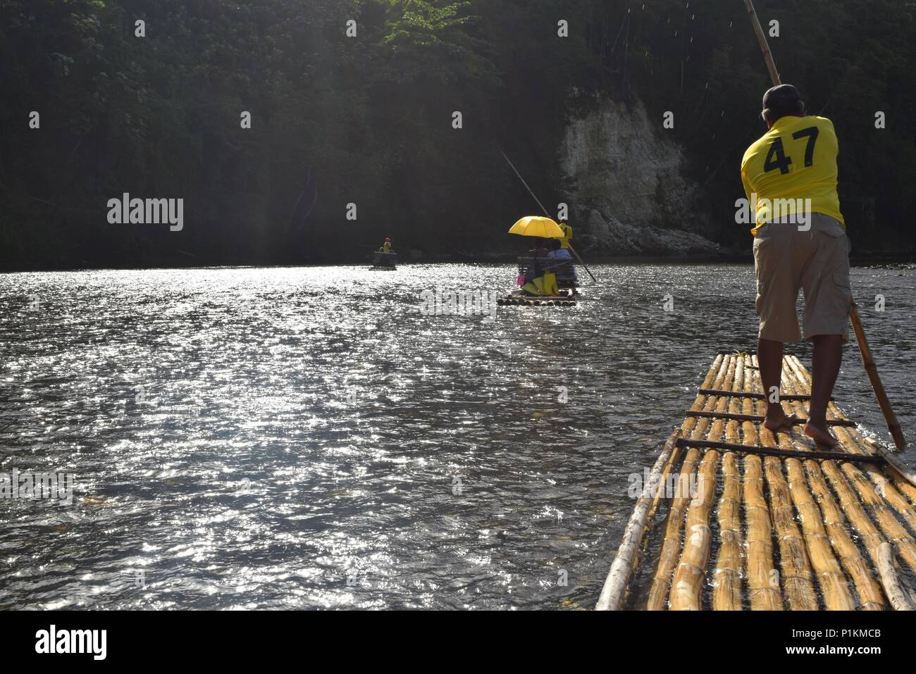 Rio Grande rafters row in sync down the river using hand-made bamboo rafts - Stock Image