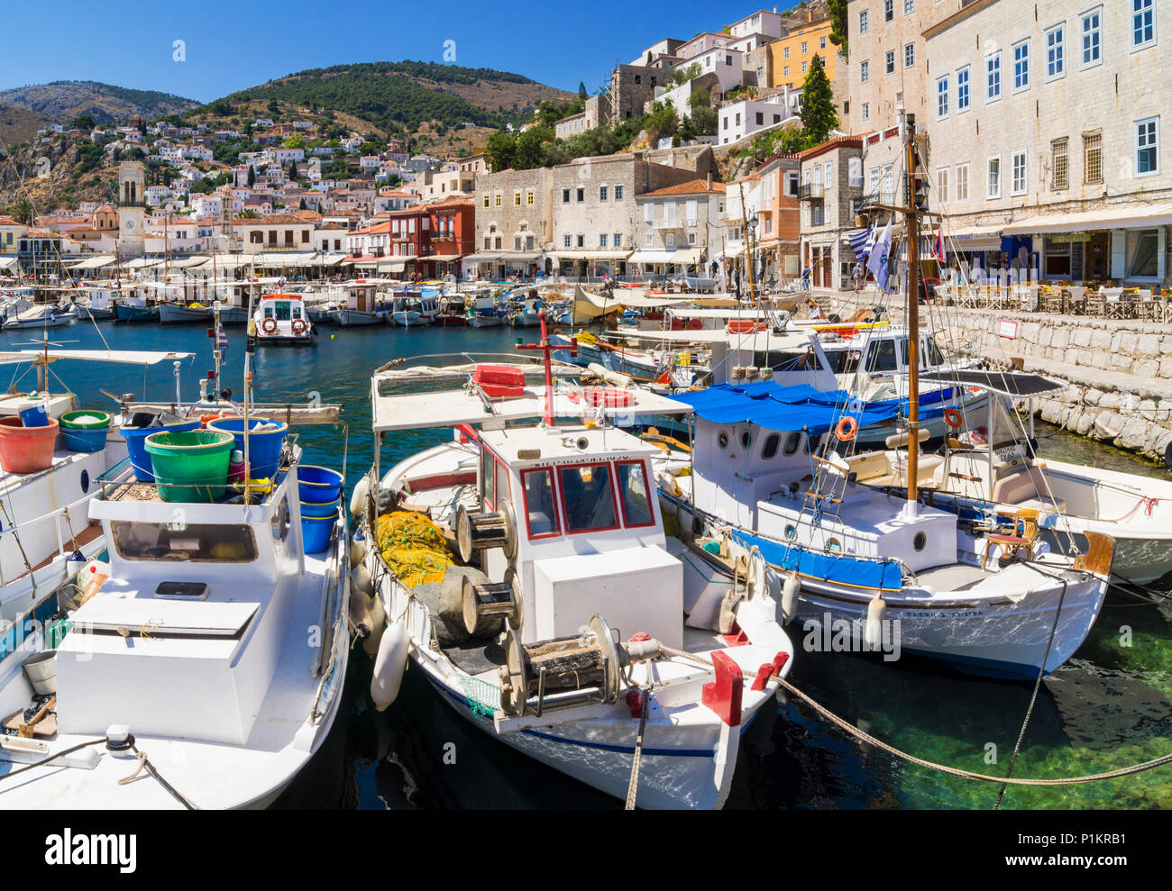 Hydra Town harbour filled with small fishing boats overlooked by the cafe lined waterfront, Hydra Island, Greece - Stock Image