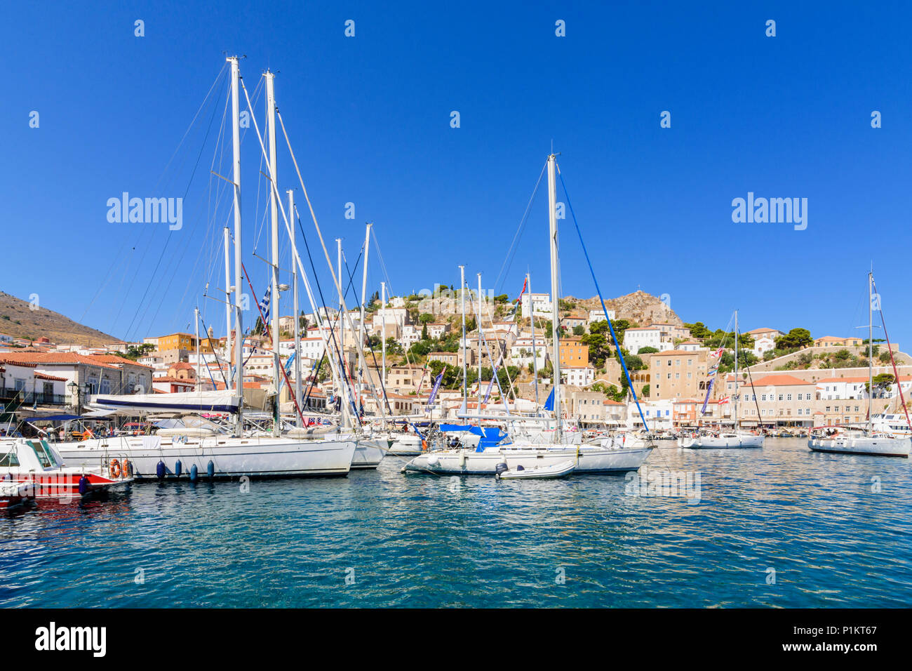 Hydra Town harbour filled yachts overlooked by the cafe lined waterfront, Hydra Island, Greece - Stock Image
