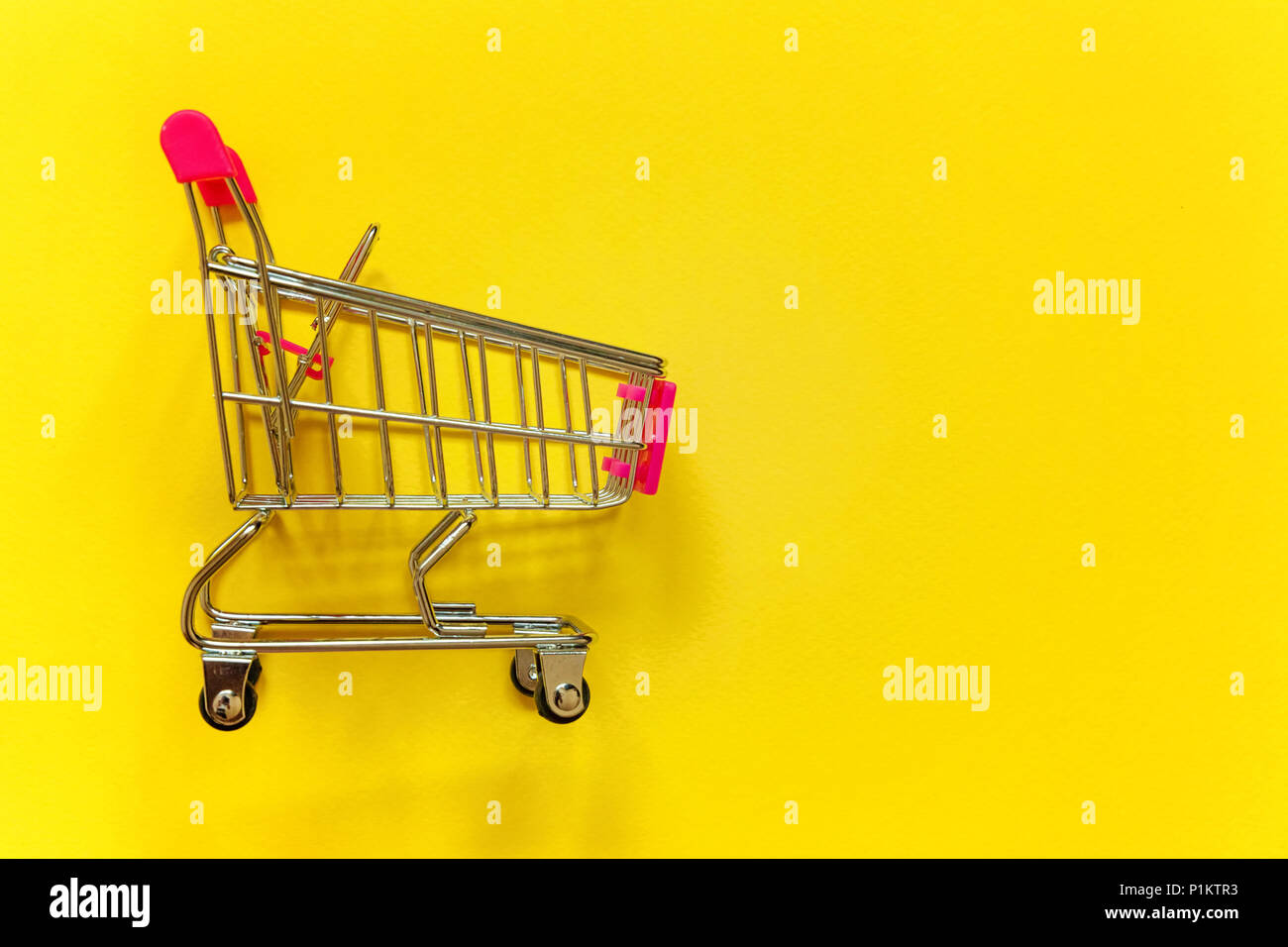 Small supermarket grocery push cart for shopping toy with wheels and pink plastic elements on yellow colourful trendy modern fashion background. Copy  Stock Photo