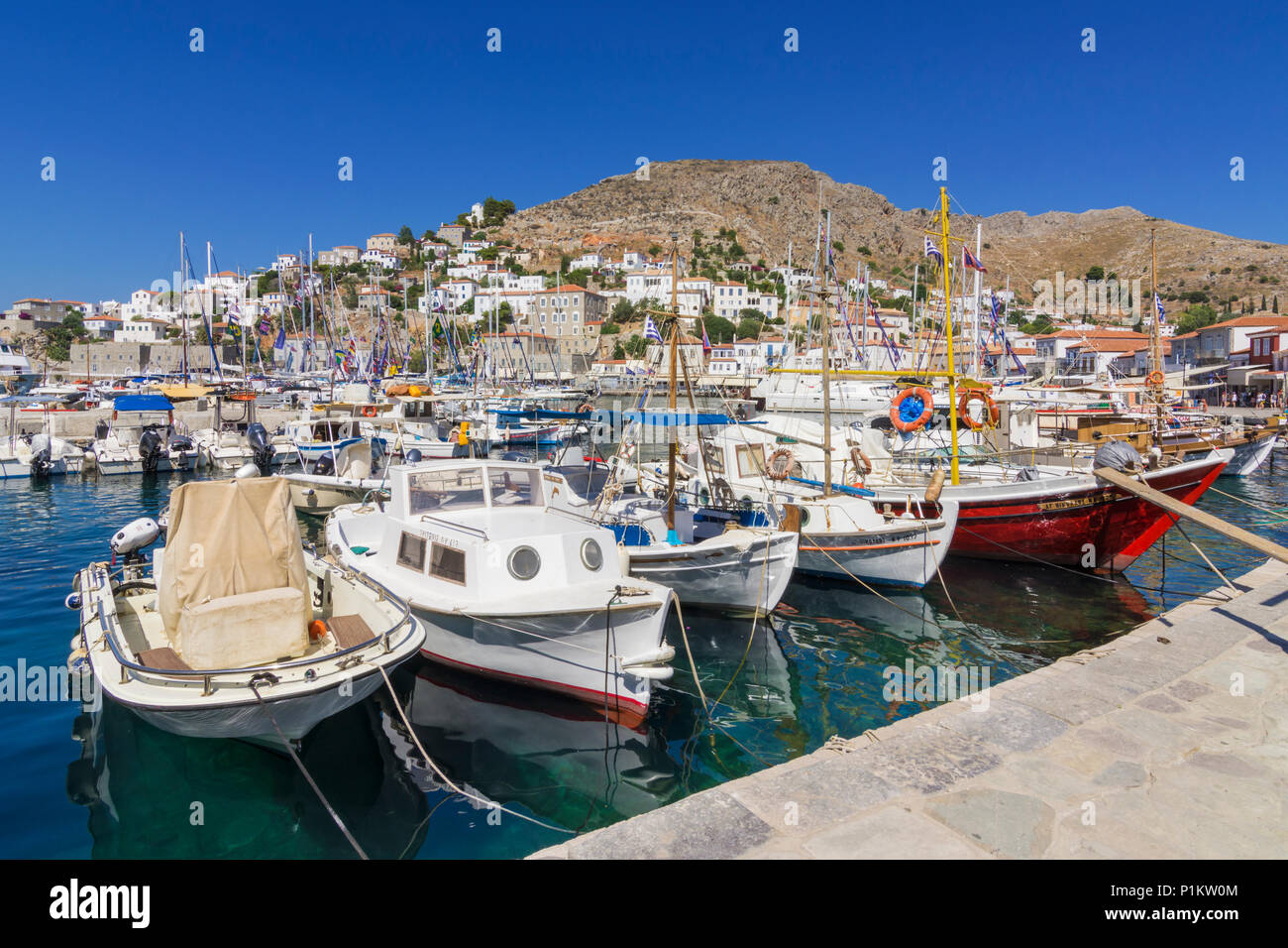 Hydra Town harbour filled with small fishing boats overlooked by the cafe lined waterfront, Hydra, Greece - Stock Image