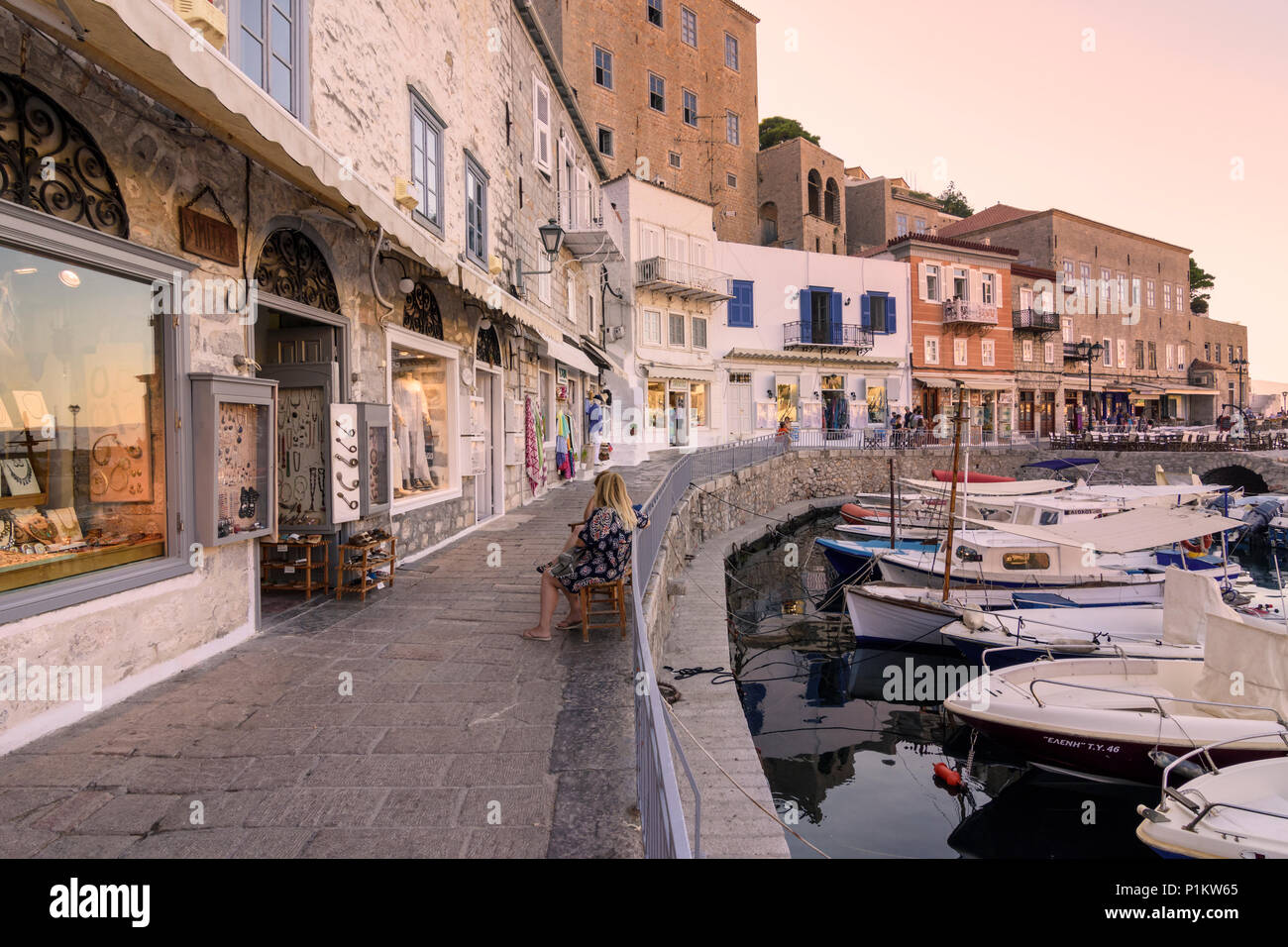 Hydra Town waterfront shops at sunset, Hydra Island, Greece - Stock Image