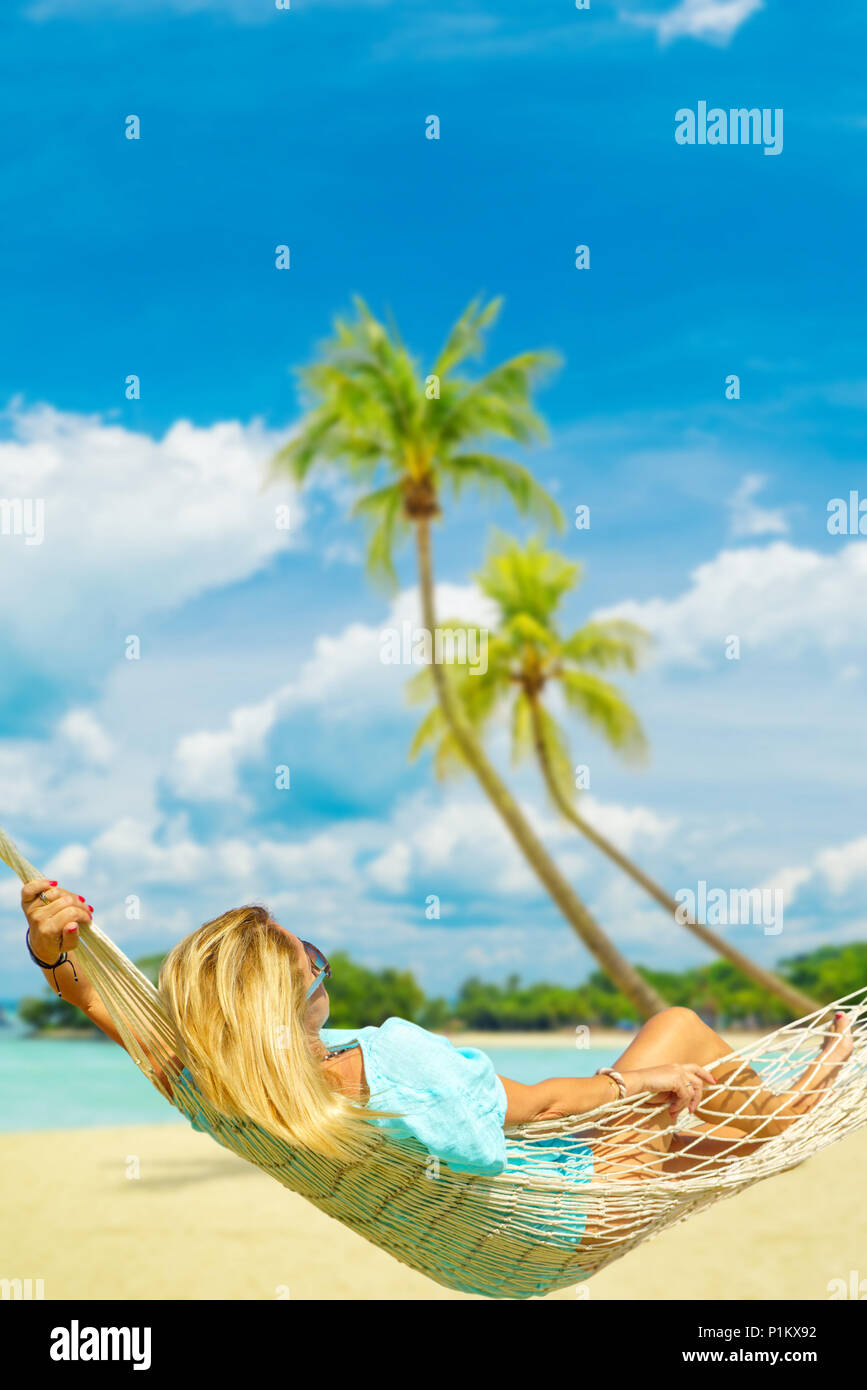 woman relaxing at the beach on a hammock on sentosa beach stock