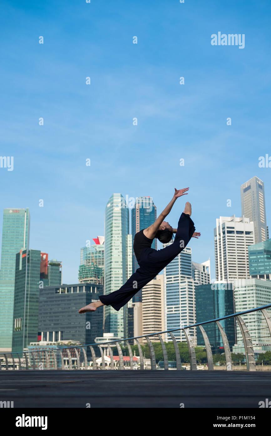 Elegant ballet dancer woman dancing ballet in the city of Singapore - Stock Image