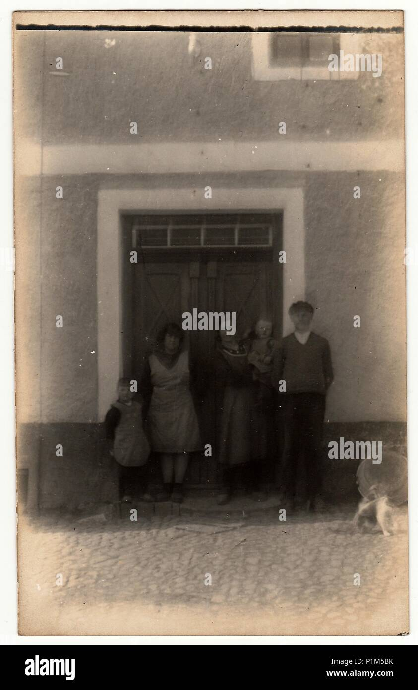 THE CZECHOSLOVAK REPUBLIC - CIRCA 1920s: Vintage photo shows a rural family in front of house. Photography contains slight blurriness. Stock Photo