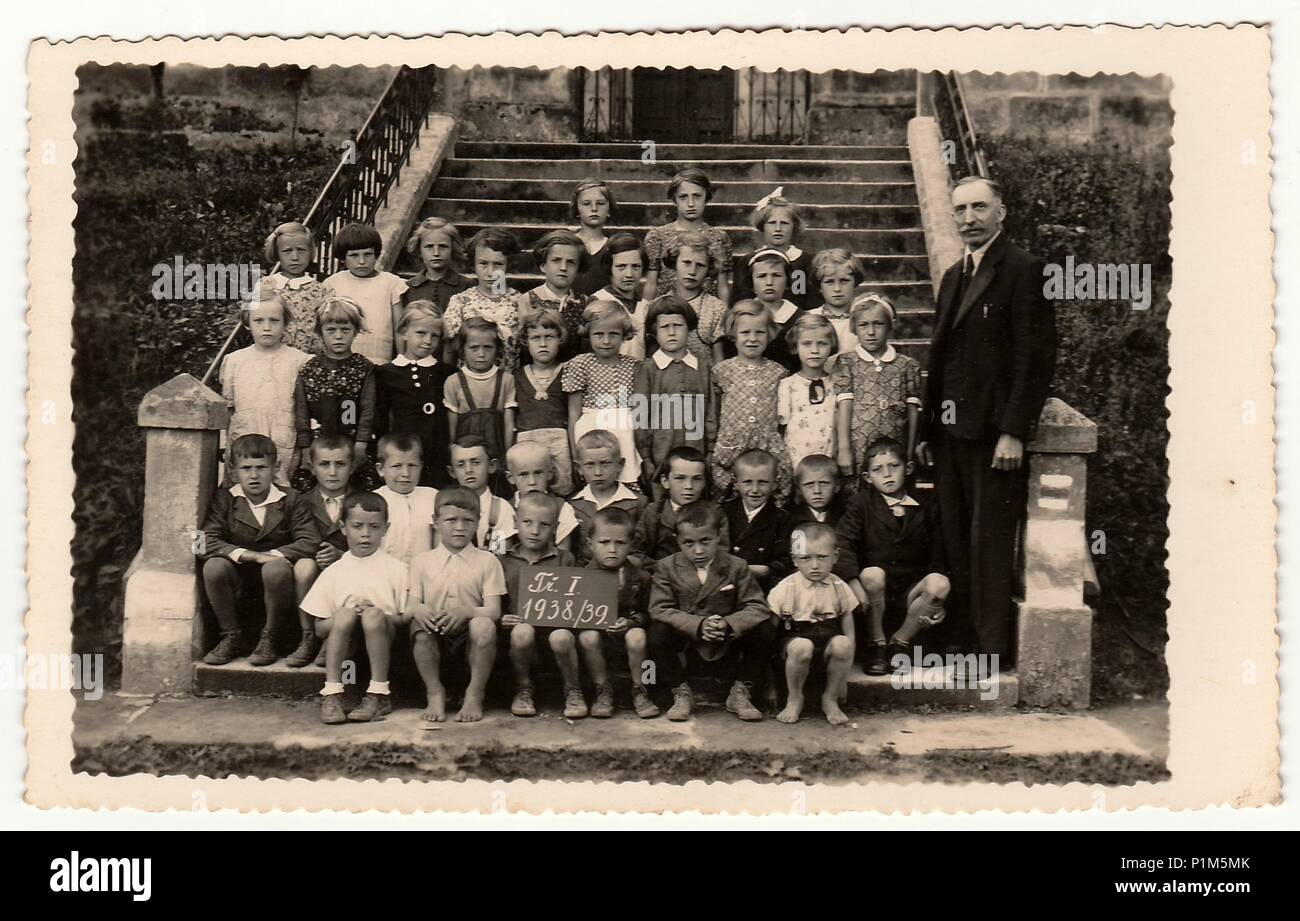 THE CZECHOSLOVAK REPUBLIC - 1939: Vintage photo shows pupils (schoolmates) and their teacher pose in front of school. Black & white antique photography. - Stock Image