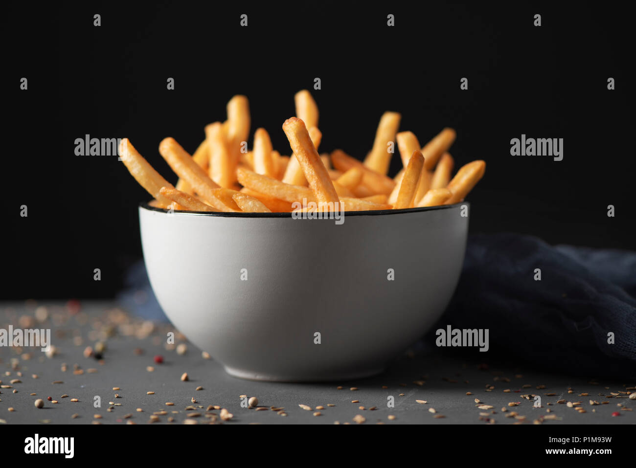 some appetizing french fries served in a white ceramic bowl, placed on a gray rustic wooden table, against a black background - Stock Image