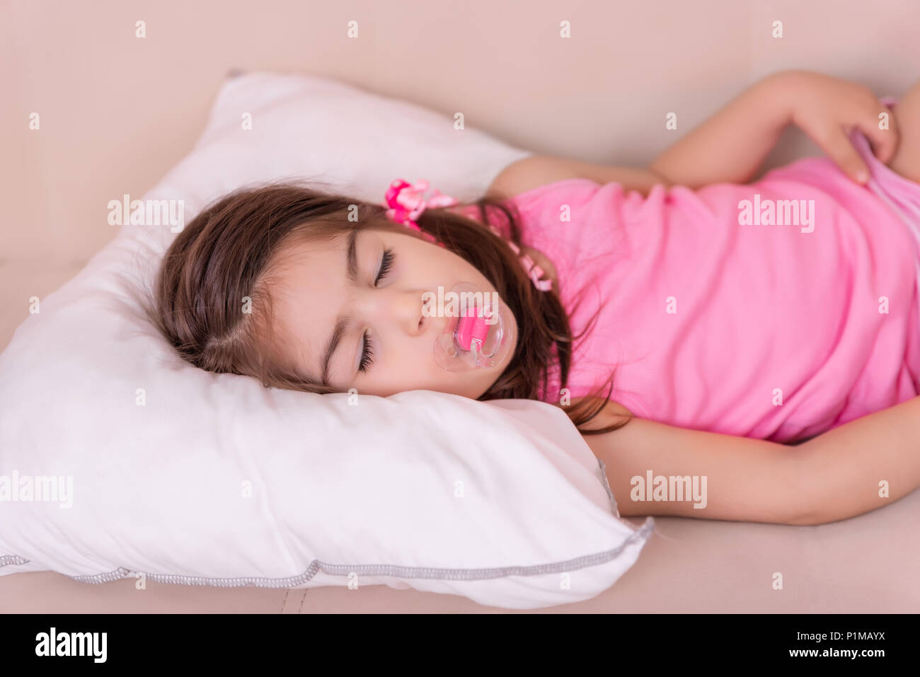 portrait of cute girl sleeps on a bed with pacifier in her mouth