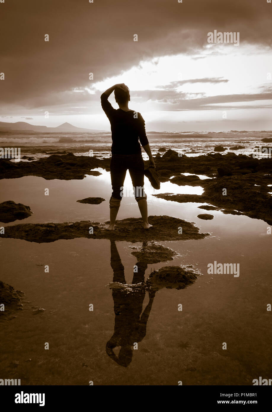 Rear view of woman holding shoes looking out to sea at sunset: meditation, mental health, loneliness, freedom, depression..concept image - Stock Image