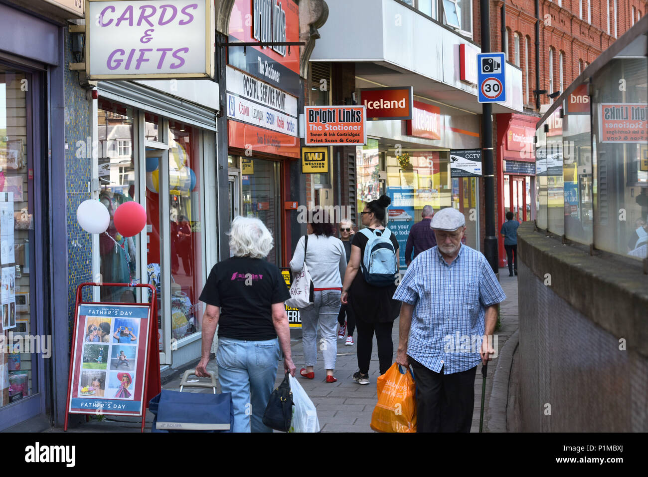 People and shoppers walk past independent and charity shops and a branch of Iceland, located on the Finchley Road High Street in North London. - Stock Image