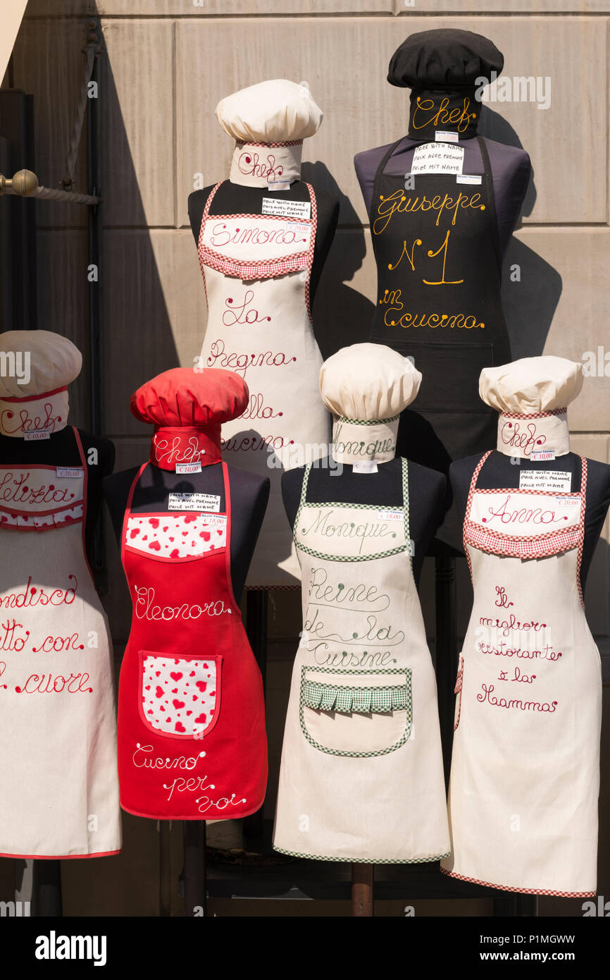 Italy Sicily Palermo display of cloth apron aprons chef hat hats personalised to order in shop store fun tourism souvenir memorabilia red white black - Stock Image