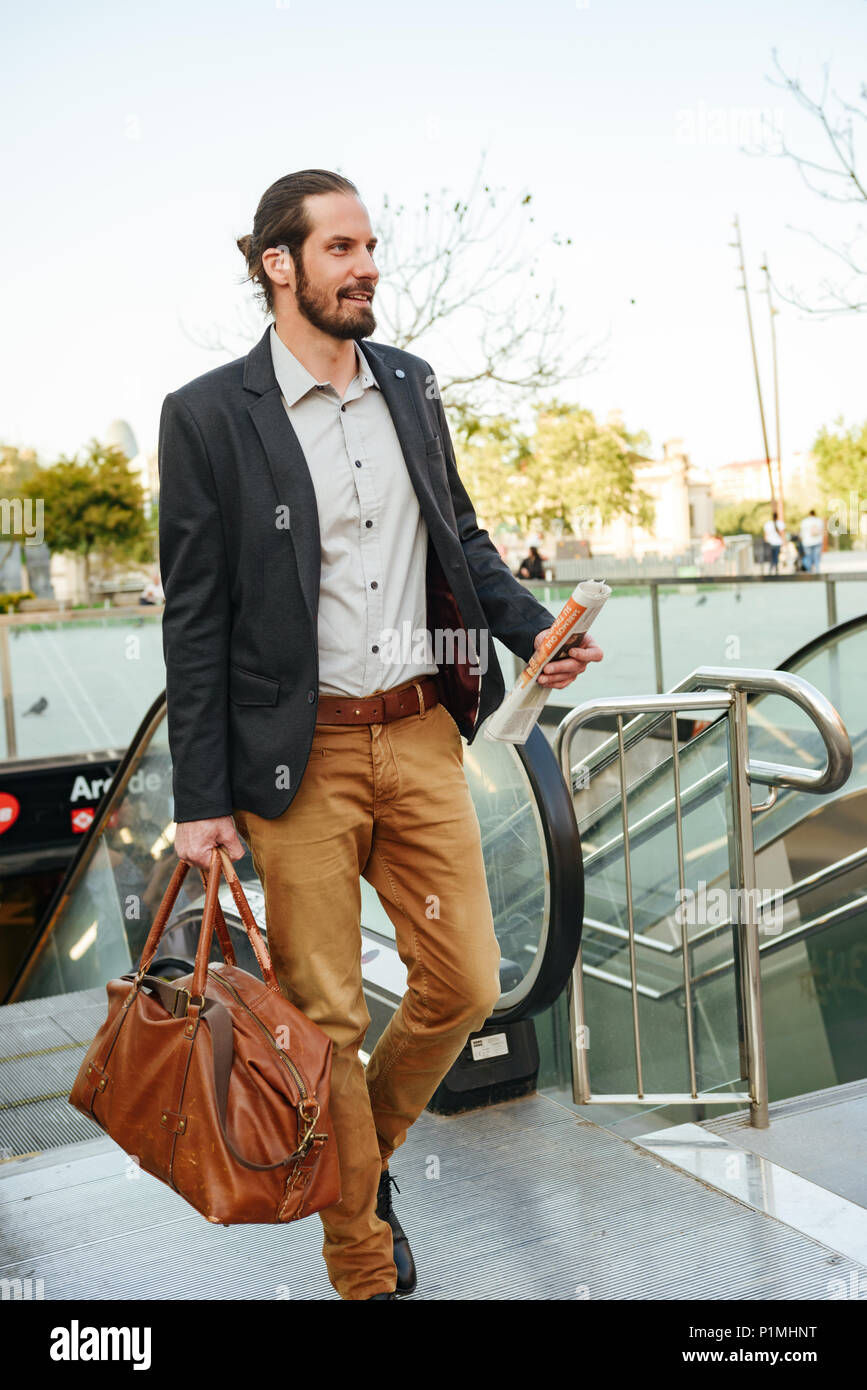 Full length image of successful businessman in stylish formal wear going up the escalator in city centre with leather male bag and newspaper in hands Stock Photo