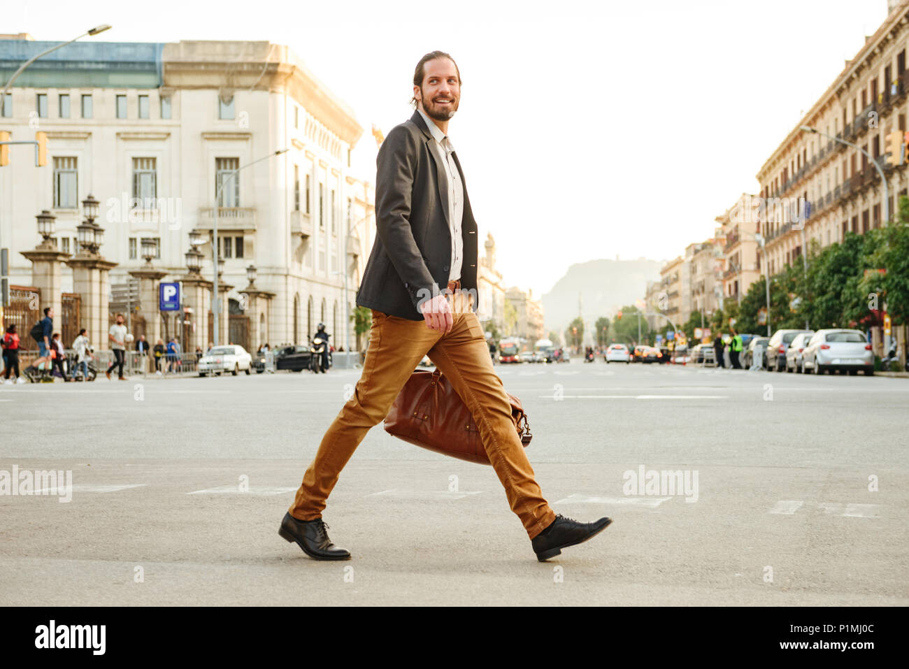 Portrait of elegant businessman in jacket laughing while crossing road in megapolis with leather male bag in hand - Stock Image