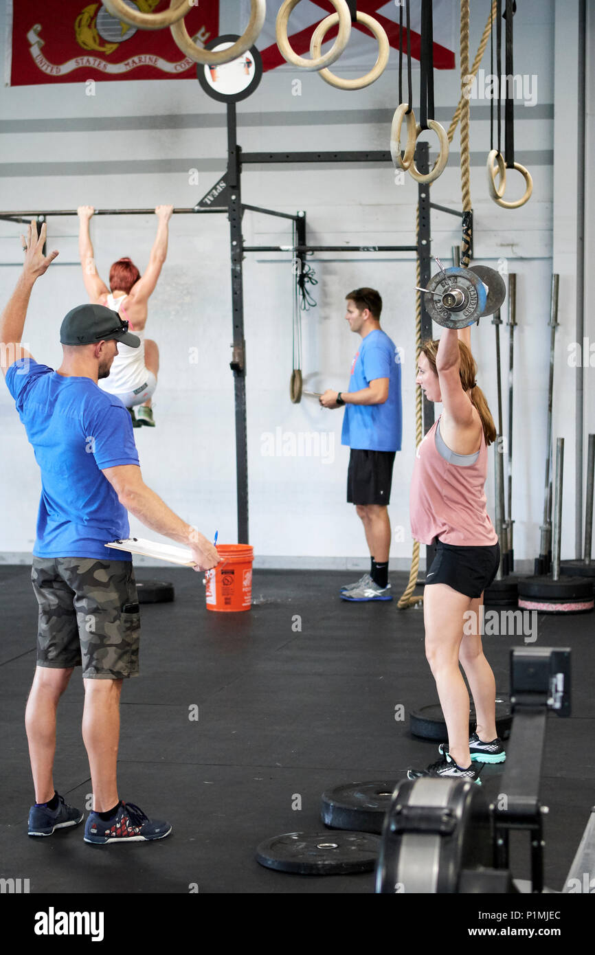 Female or woman competing in a CrossFit fitness challenge competition by dead lifting weights inside a gym in Montgomery Alabama, USA. - Stock Image