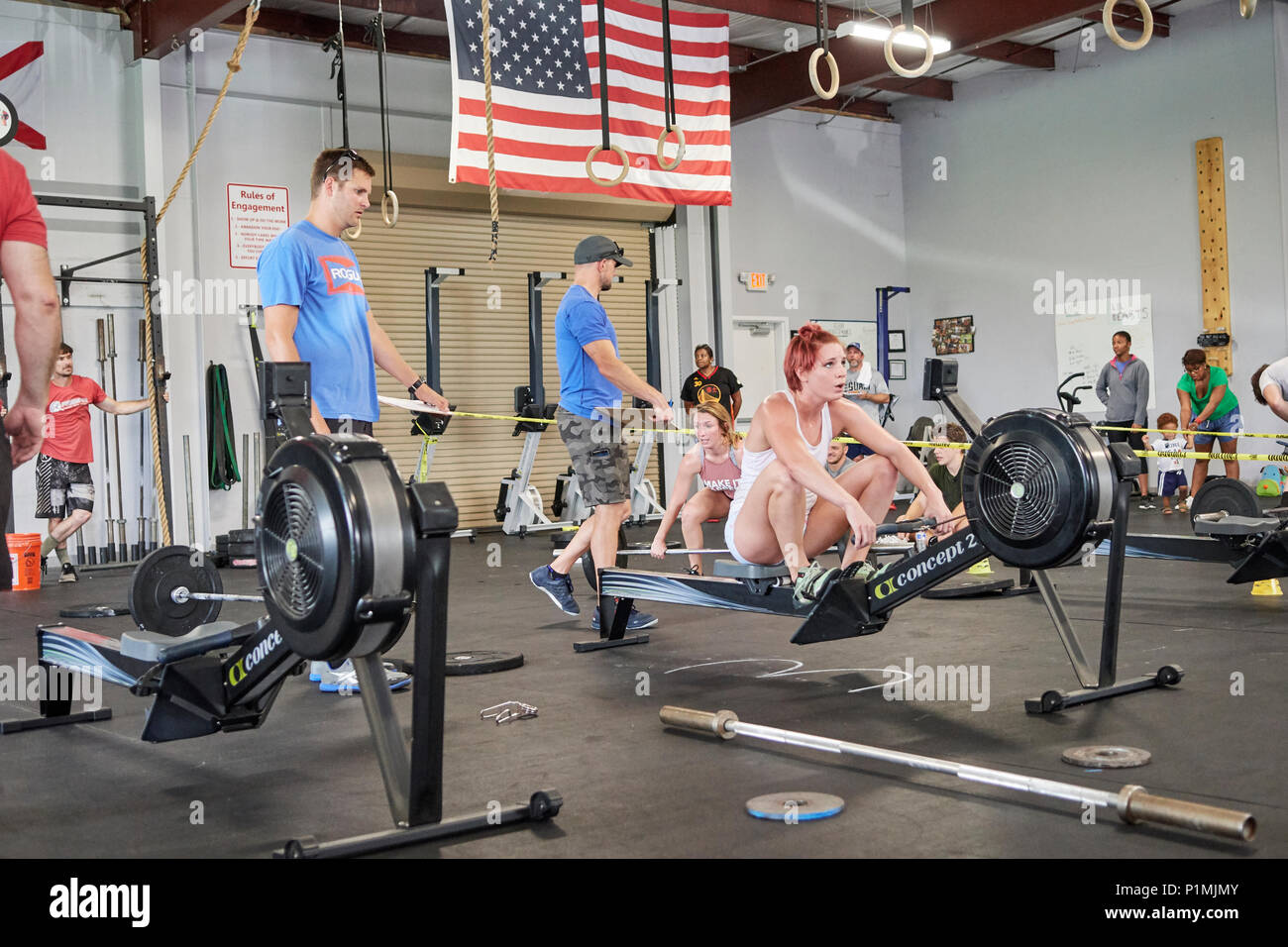 Female or woman competing in a CrossFit fitness challenge competition by using a rowing machine to exhaustion inside a gym in Montgomery Alabama, USA. - Stock Image