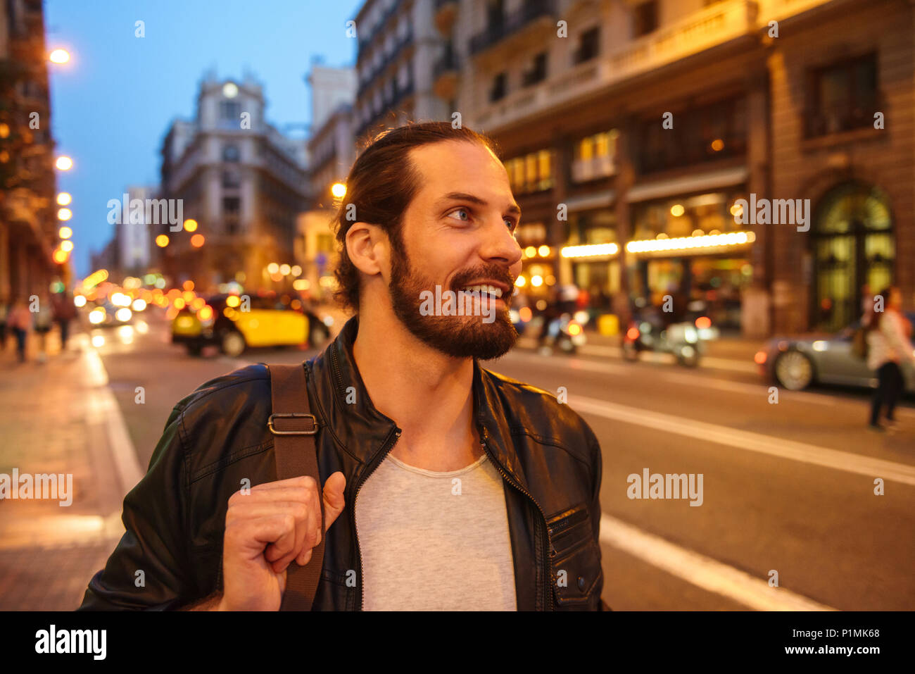 Portrait of smiling european man with tied hair looking aside while walking through megapolis in evening - Stock Image