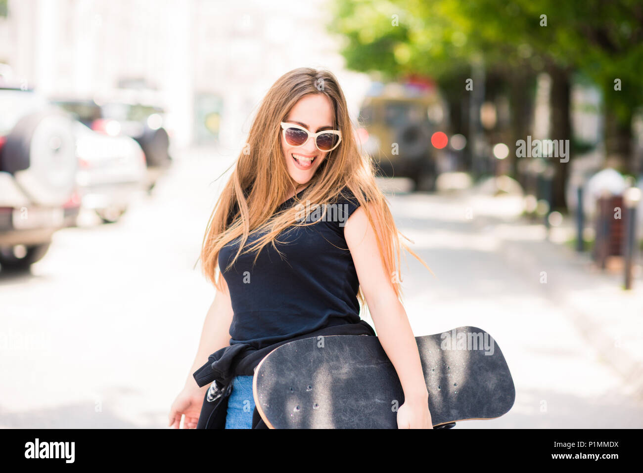 Portrait of cute teenage girl while holding her skate board - Stock Image