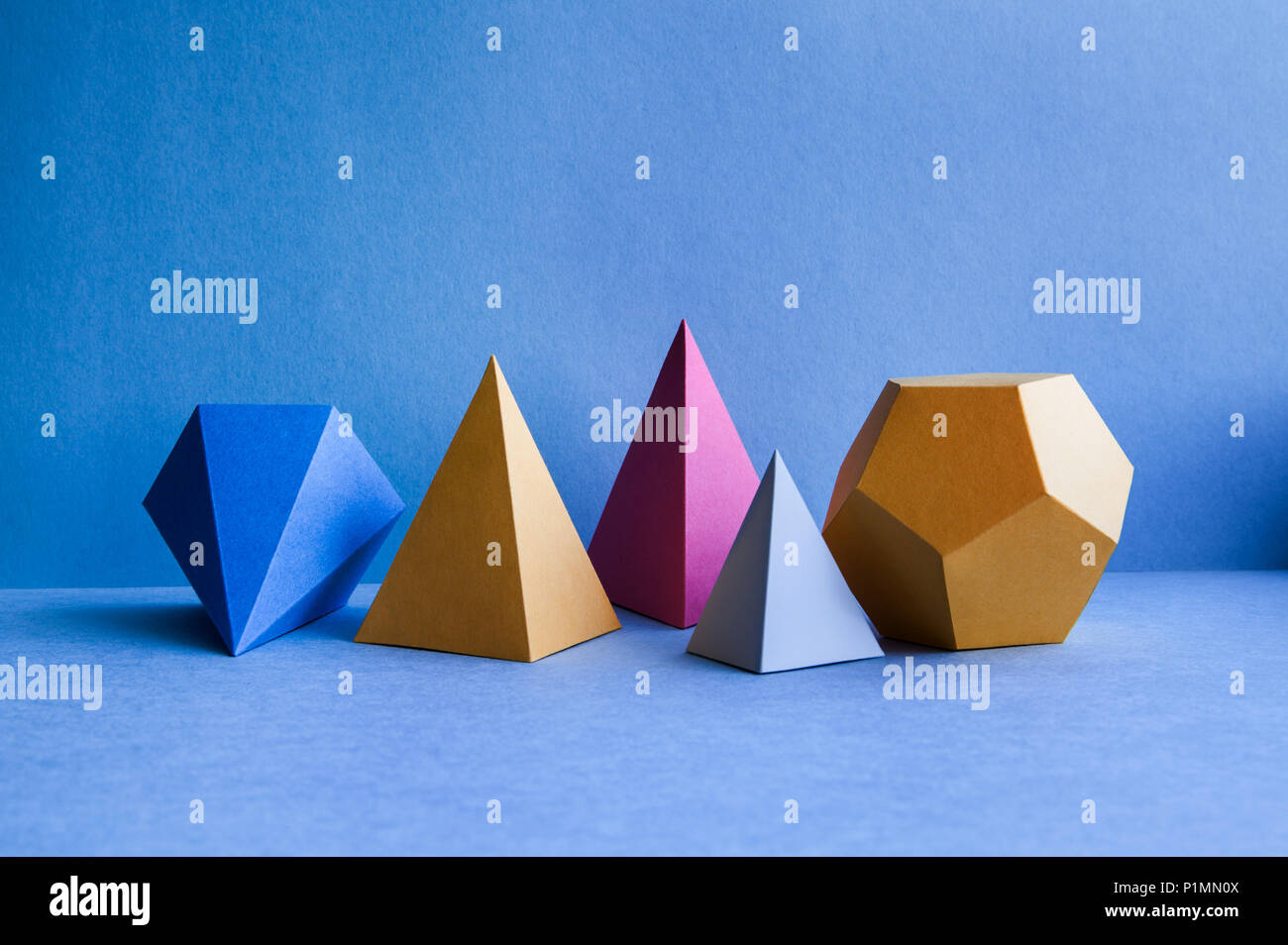 Abstract geometric figures. Three-dimensional dodecahedron pyramid tetrahedron cube rectangular objects on blue background. Bright platonic solids still life background. - Stock Image