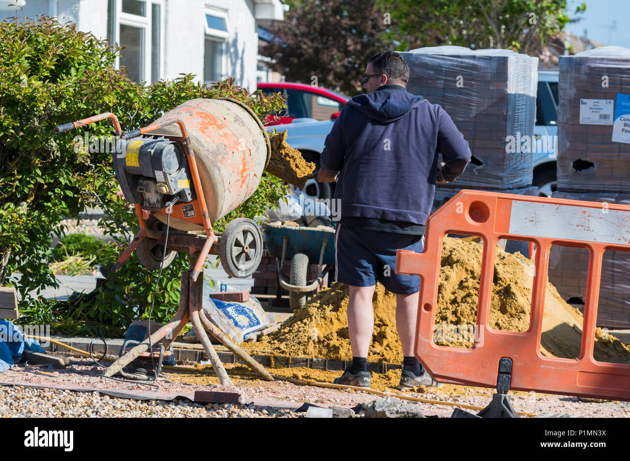 Man placing sand into a portable cement mixer as part of construction work on a residential property in the UK. - Stock Image