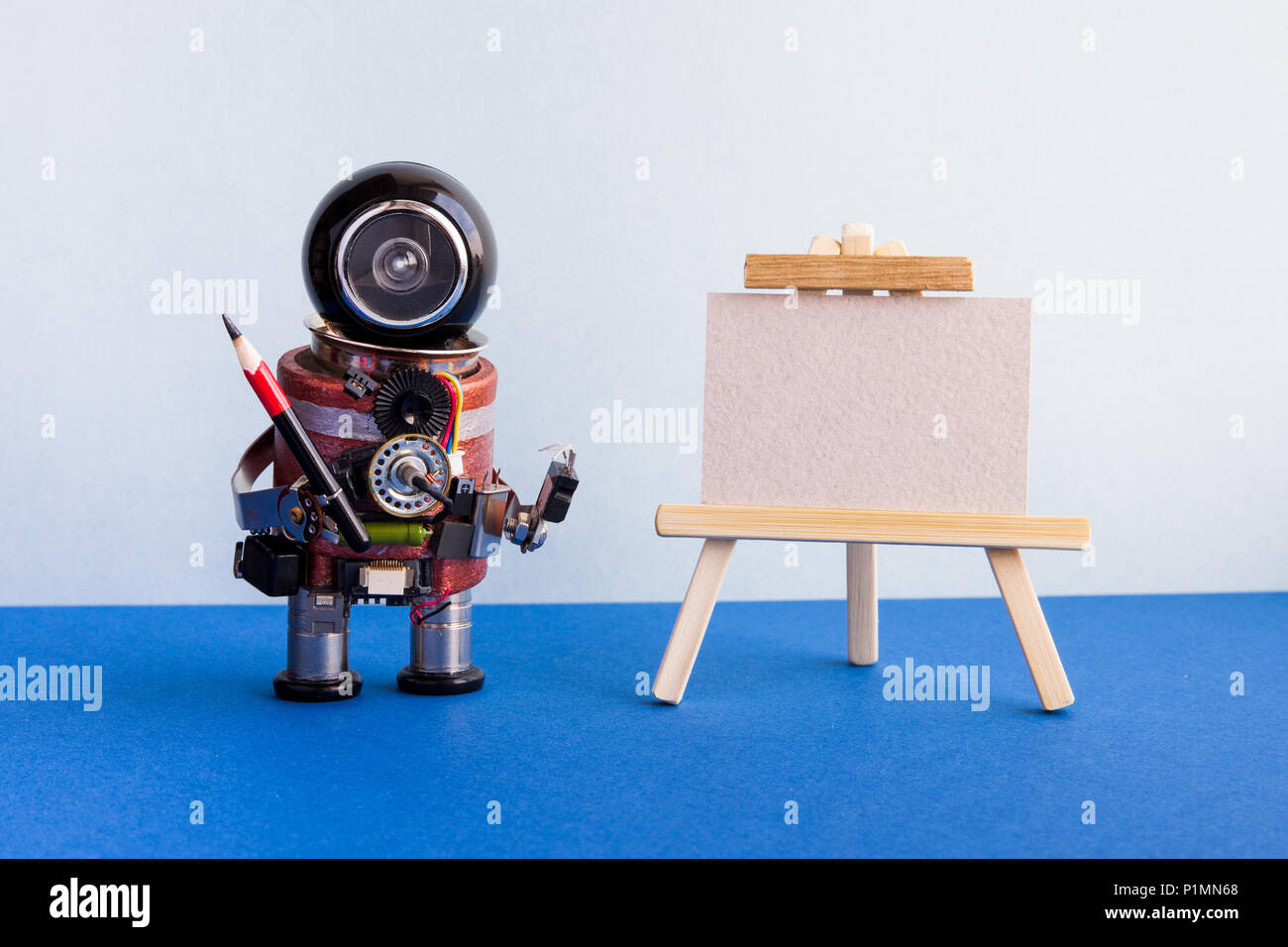 Kindly robot artist begins to create a drawing with a pencil. White paper template, wooden easel. Advertising poster studio school of visual arts. copy space. - Stock Image