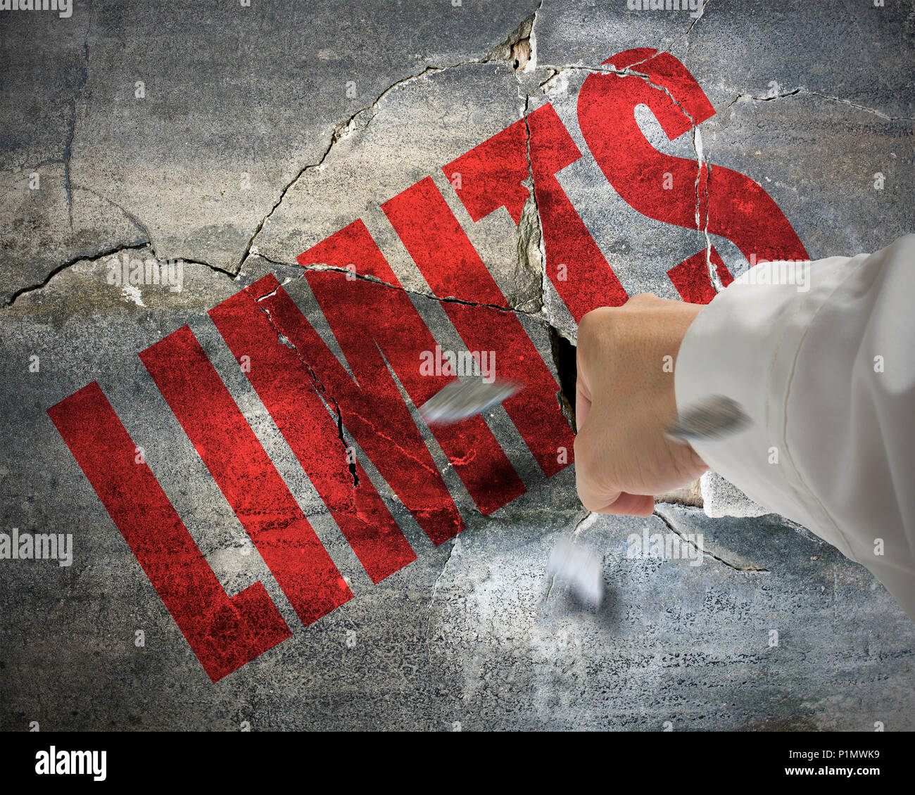 Punching, cracked concrete wall with word LIMITS on it and small pieces rock flying out - Stock Image