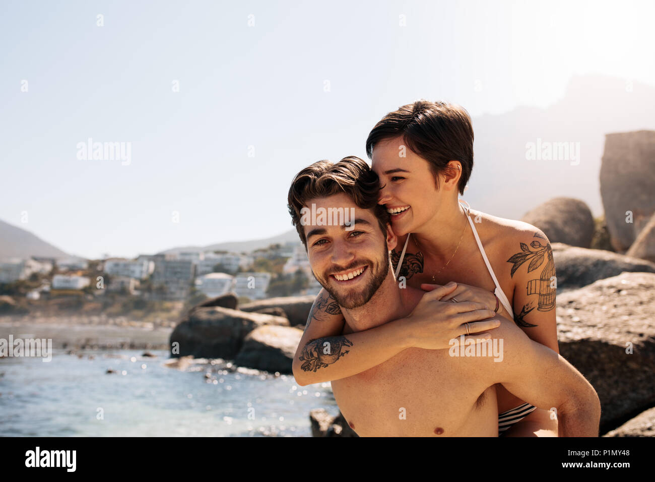 Man carrying woman on his back at the beach on a holiday. Tourist couple in a happy and romantic mood enjoying a holiday. - Stock Image