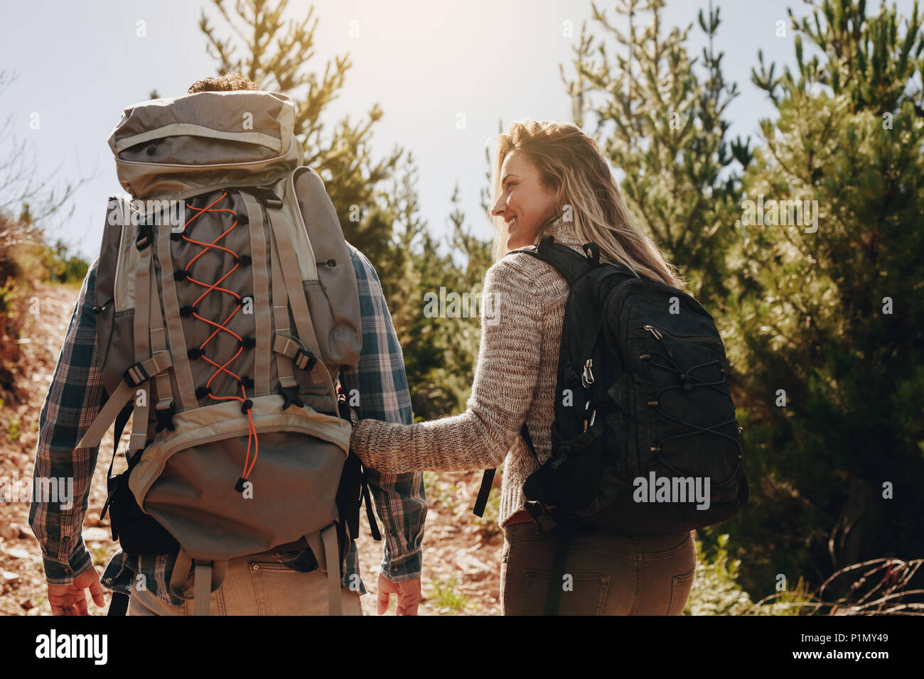 Rear view of couple of young people hiking. Young man and woman with their backpacks hiking on mountain. - Stock Image