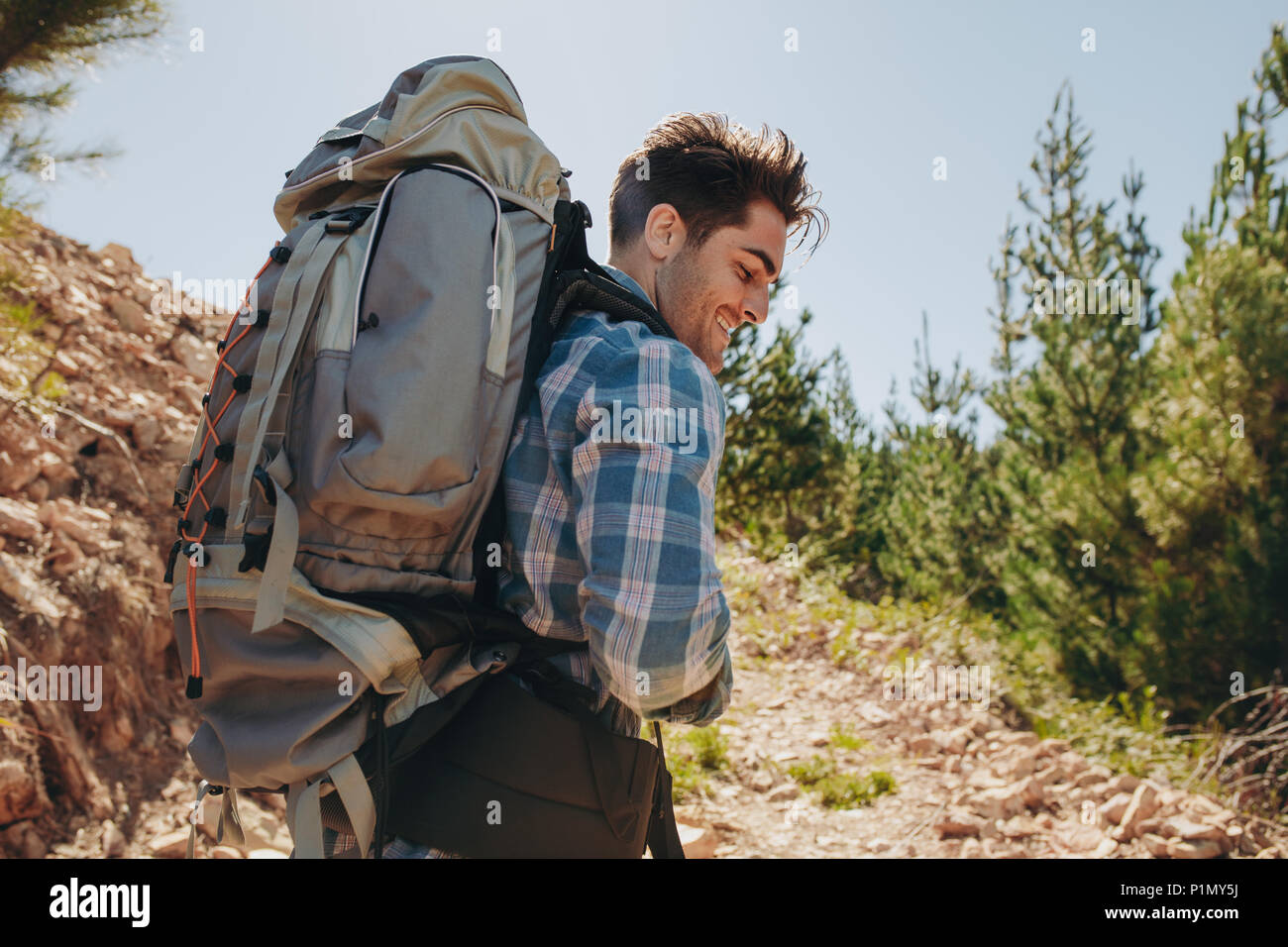 Rear view shot of smiling young guy with backpack hiking on mountains. Caucasian male hiker trekking on mountain. - Stock Image