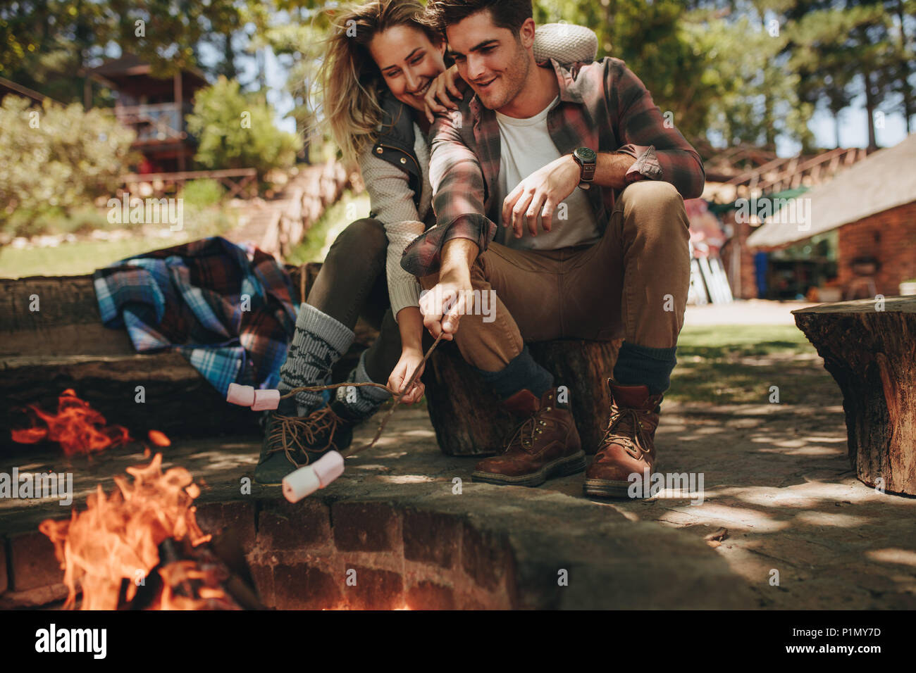 Couple roasting marshmallows on bonfire at campsite. Man and woman having roasted sweets on camping. - Stock Image