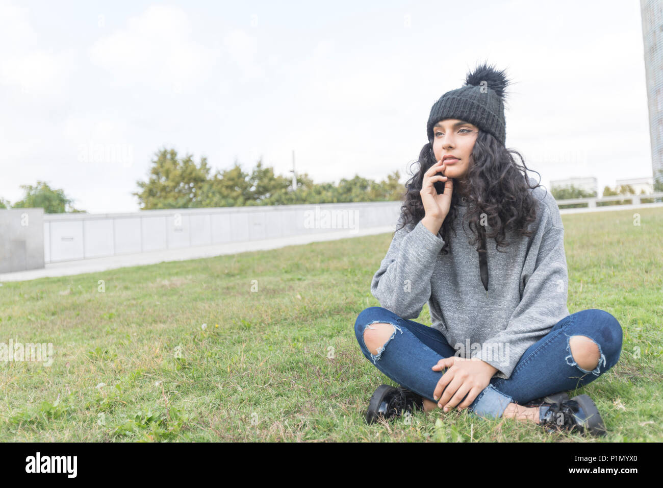 portrait of a woman with wool cap and sweater sitting on a grass garden - Stock Image