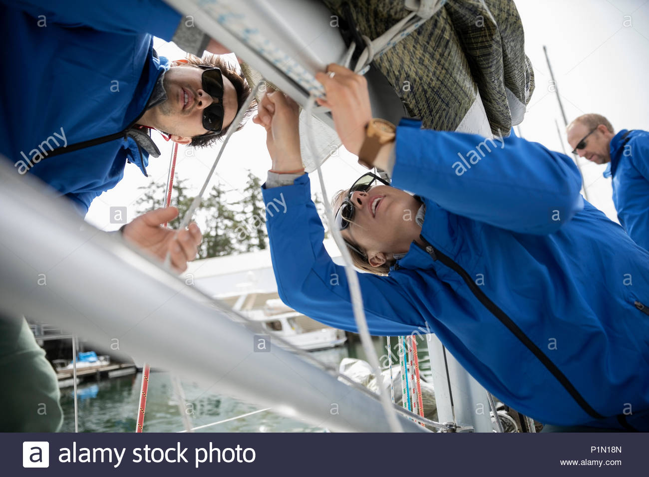 Sailing team preparing sail on sailboat - Stock Image