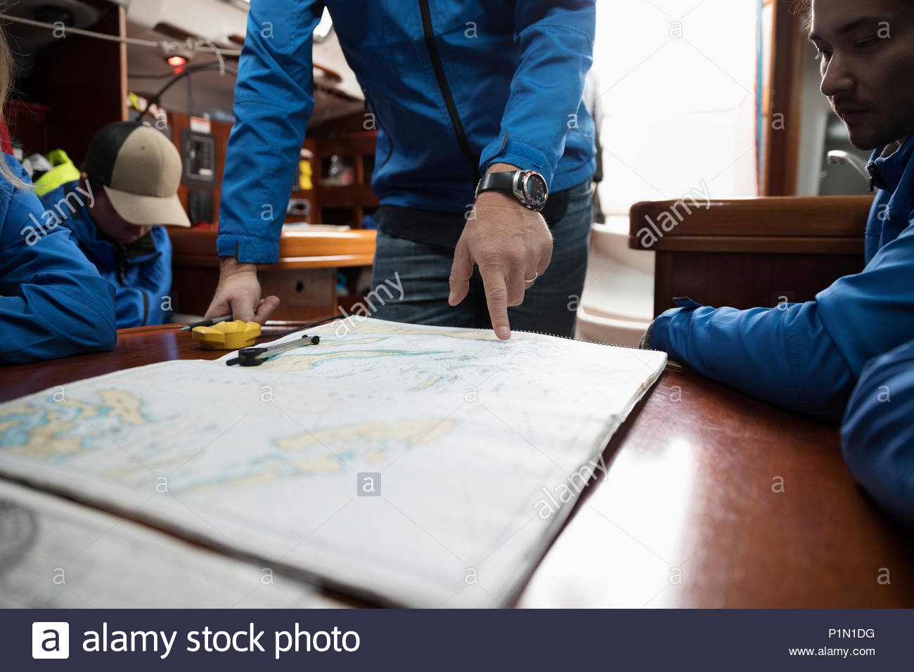 Sailing team plotting course at map on sailboat - Stock Image