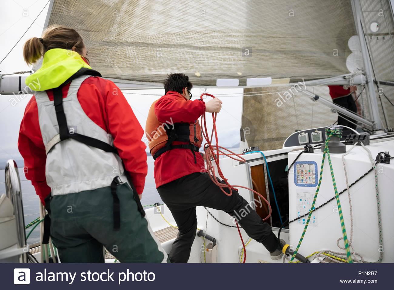 Sailing team adjusting rigging rope on sailboat - Stock Image