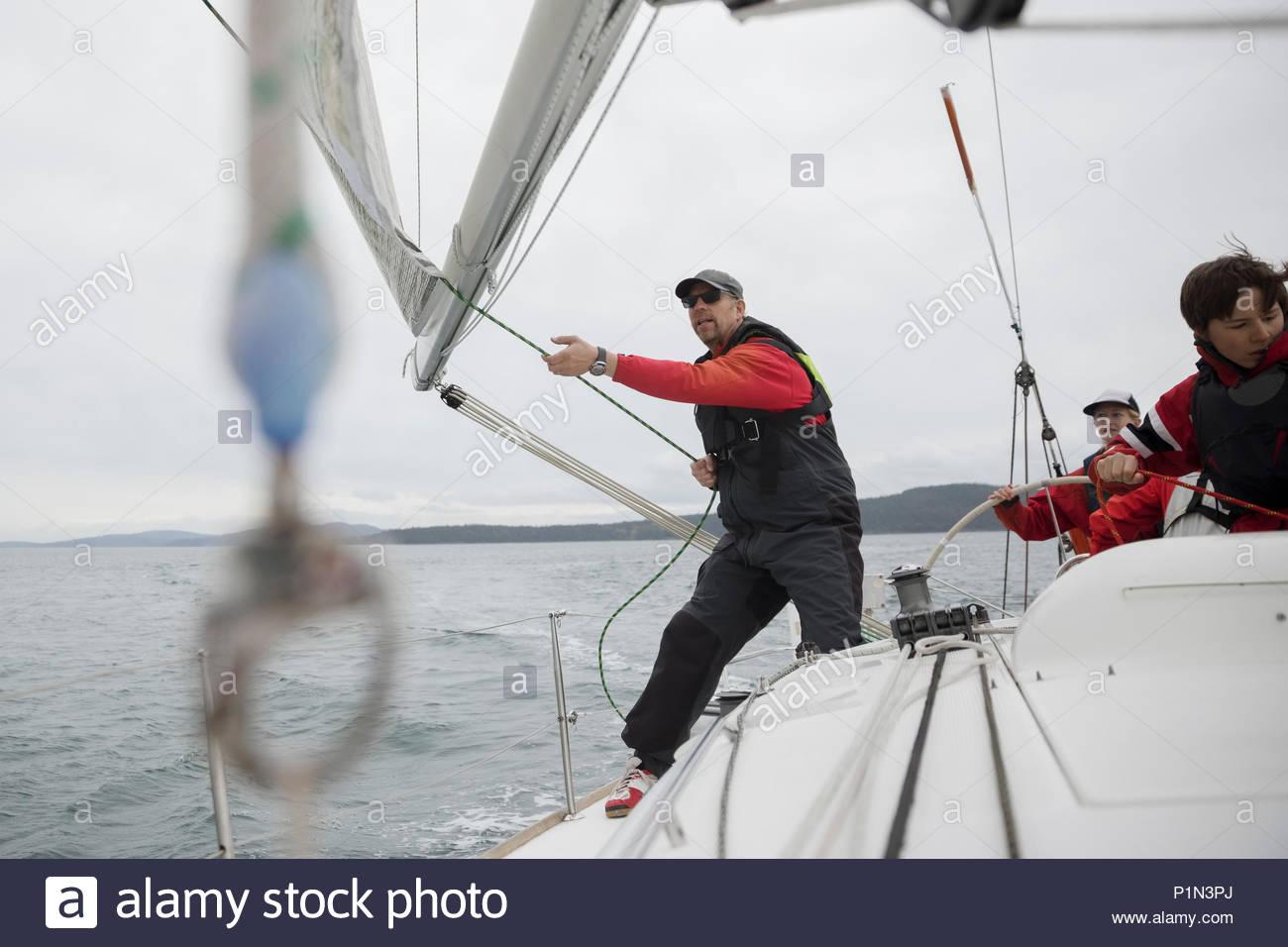 Sailing team training on sailboat on ocean - Stock Image