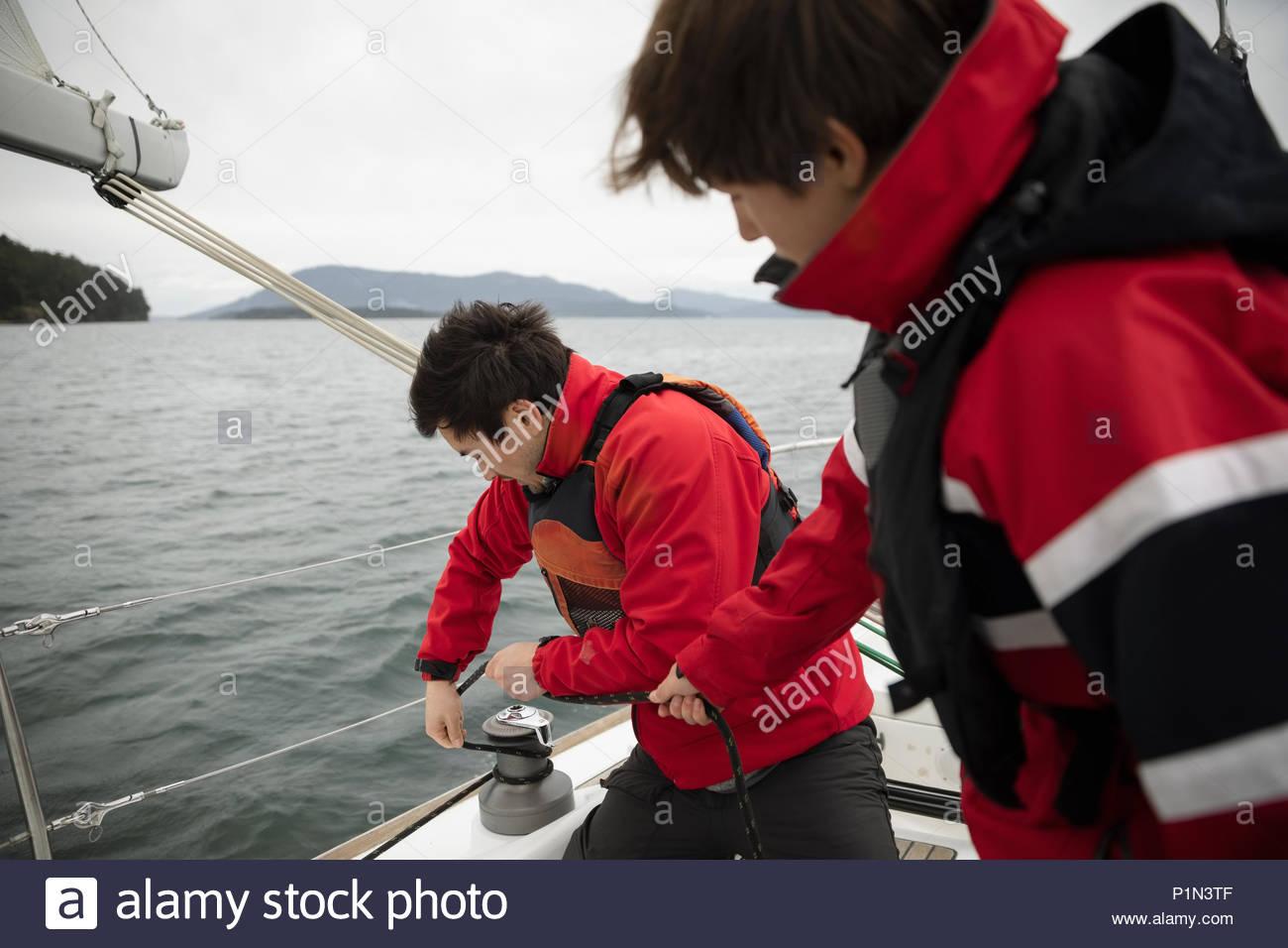 Sailing team adjusting equipment on sailboat on ocean - Stock Image
