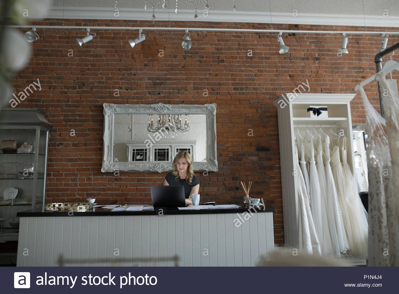 Bridal boutique owner working at laptop - Stock Image