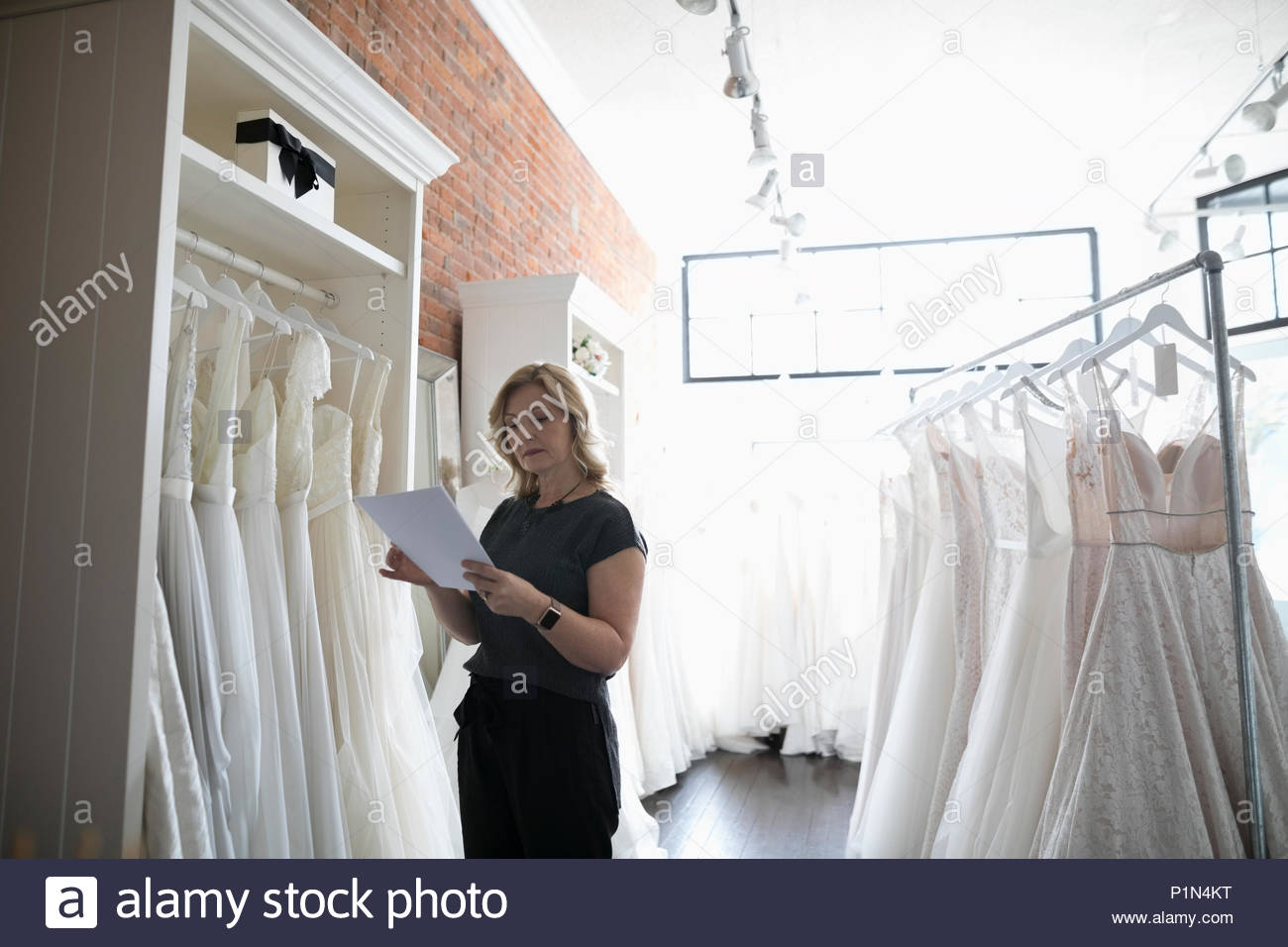 Bridal boutique owner checking wedding dress inventory - Stock Image