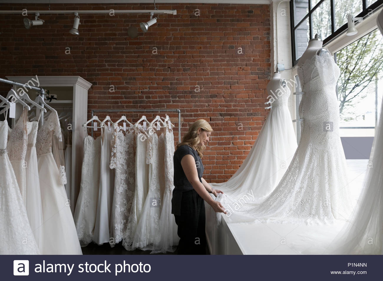 Bridal boutique owner arranging wedding dress window display - Stock Image