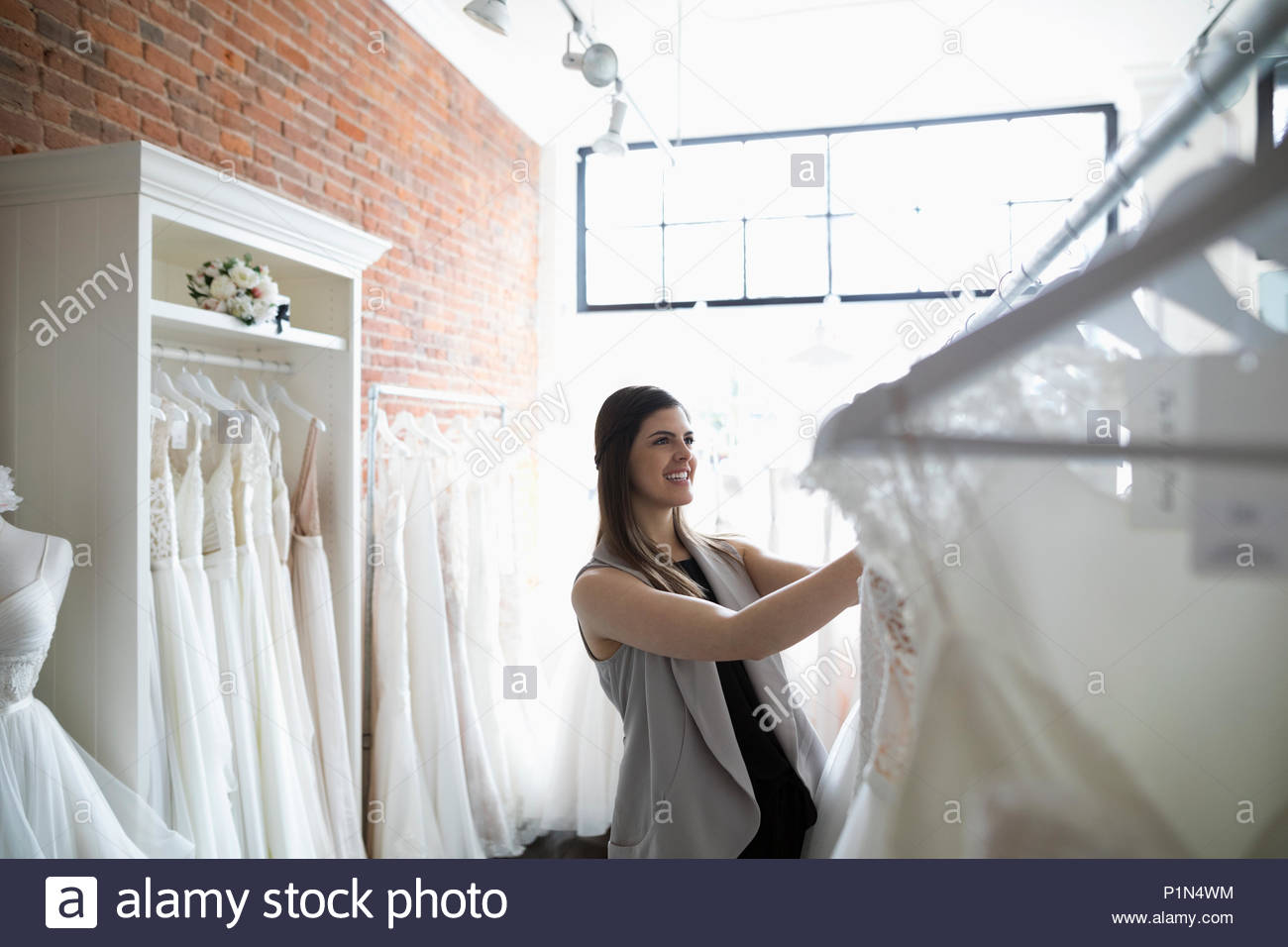 Bride shopping for wedding dresses in bridal boutique - Stock Image