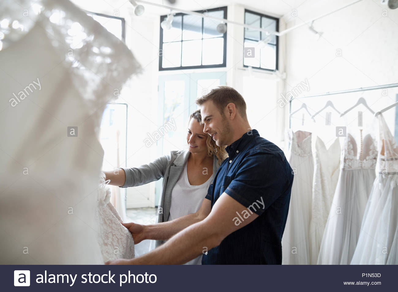 Bride and groom shopping for wedding dresses in bridal boutique Stock Photo