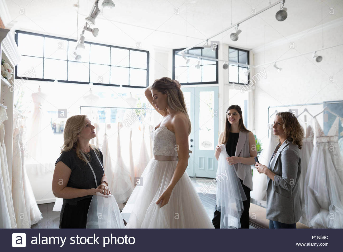 Bride and friends at wedding dress fitting in bridal boutique - Stock Image