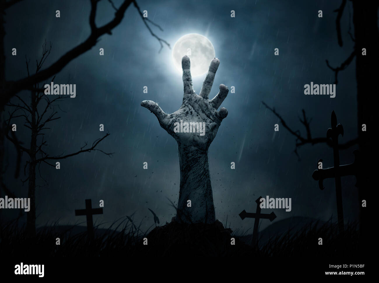 Halloween concept, dead hand coming out from the soil - Stock Image