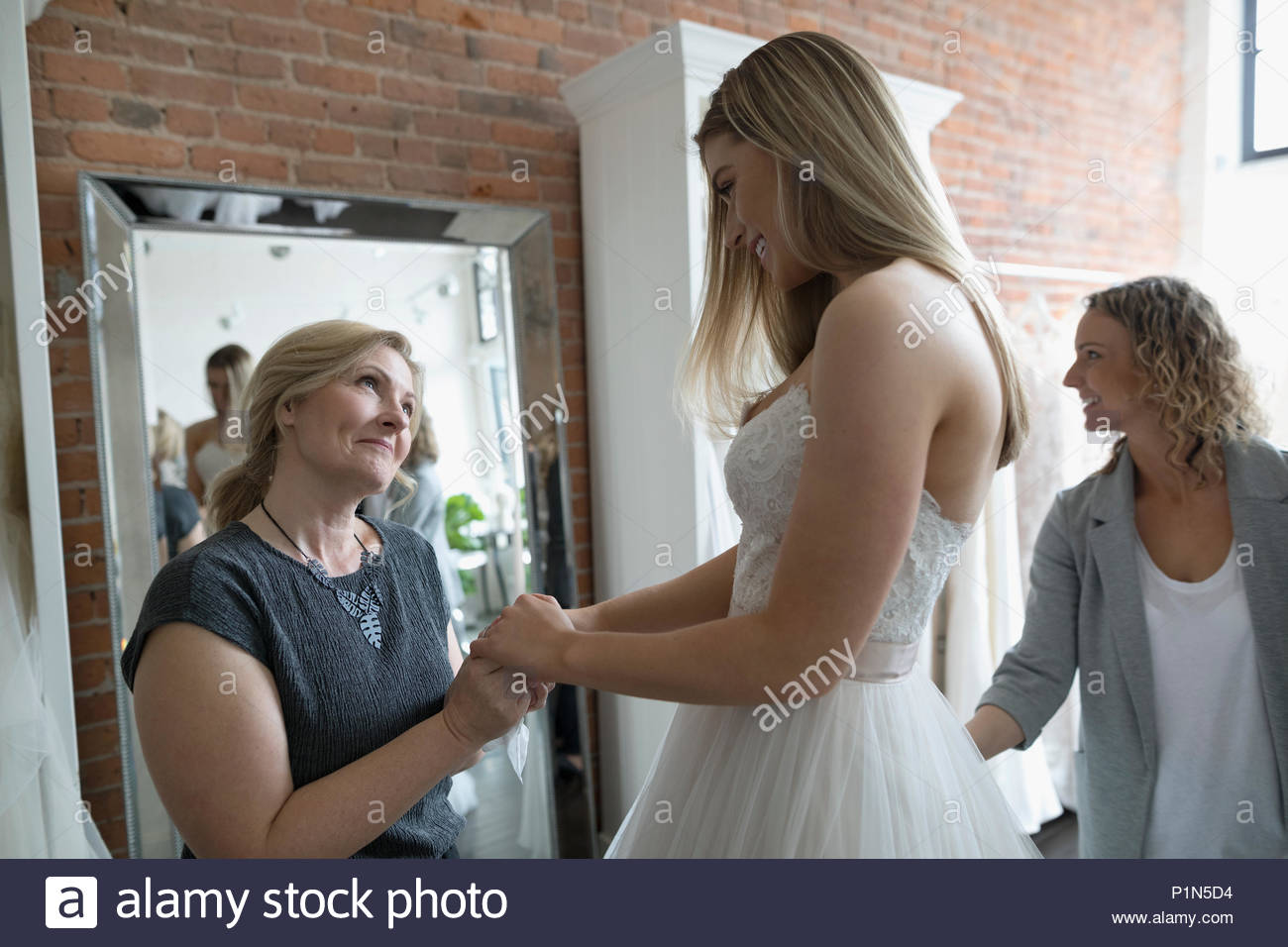 Bride and affectionate mother at wedding dress fitting in bridal boutique - Stock Image
