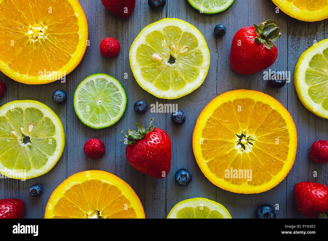 Mixed Sliced Oranges, Lemons and Limes with Blueberries and Strawberries on Blue Table - Stock Image