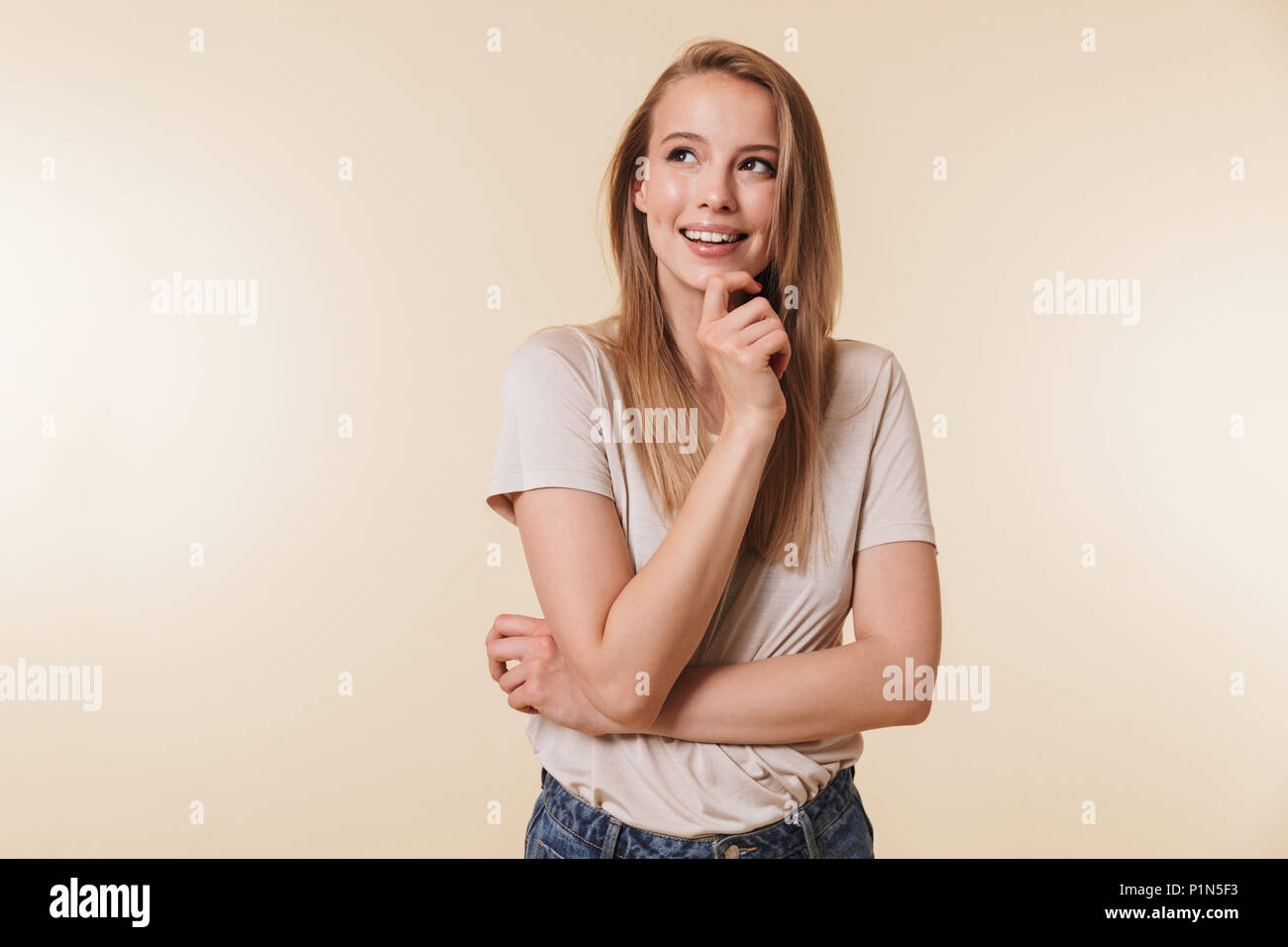 Image of affable blond woman 20s wearing casual t-shirt smiling and looking upward while standing with arms crossed isolated over beige background in  - Stock Image