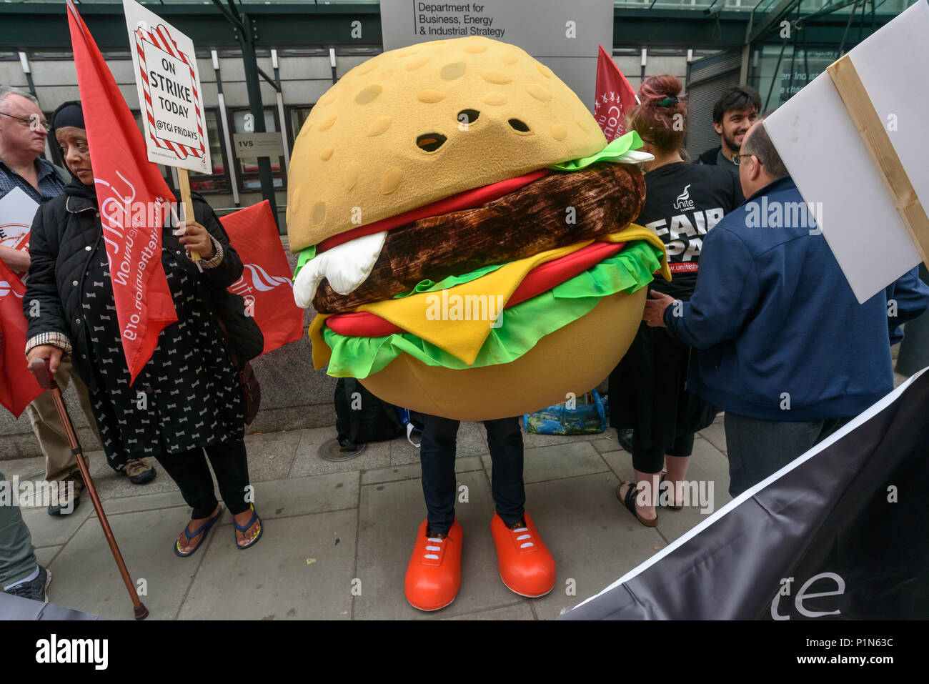 London, UK. 12th June 2018. Strikers from TGI Fridays, others from the Unite  Restaurant, Catering and Bar Workers Branch and Unite Community came to the Department of Business, Energy, Innovation and Skills with a man dressed as a giant burger to deliver a letter to business secretary Greg Clark calling on him to put an end to employers taking a part of the credit card tips that customers leave. Two years ago his predecessor Sajid Javid promised to tackle the problem but nothing has been done. Credit: Peter Marshall/Alamy Live News - Stock Image